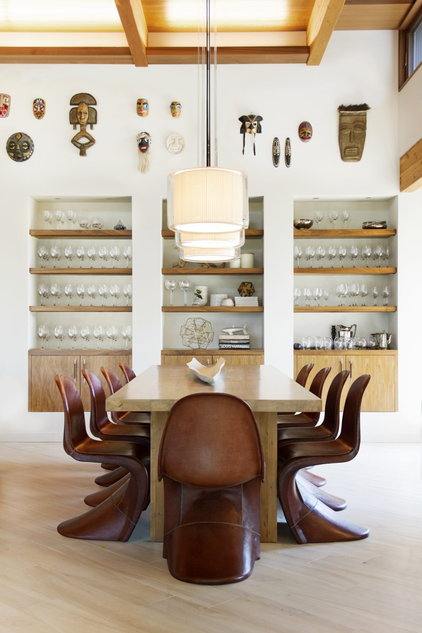 In the dining area, leather chairs from Jayson Home are arranged around the clients' table underneath a row of suspension lightsfrom Marset. Above the built-in black walnut shelving constructed by Karma Dog Construction, the designers hung various masks that the clients had collected on their travels. The floor tile is from Designtra.
