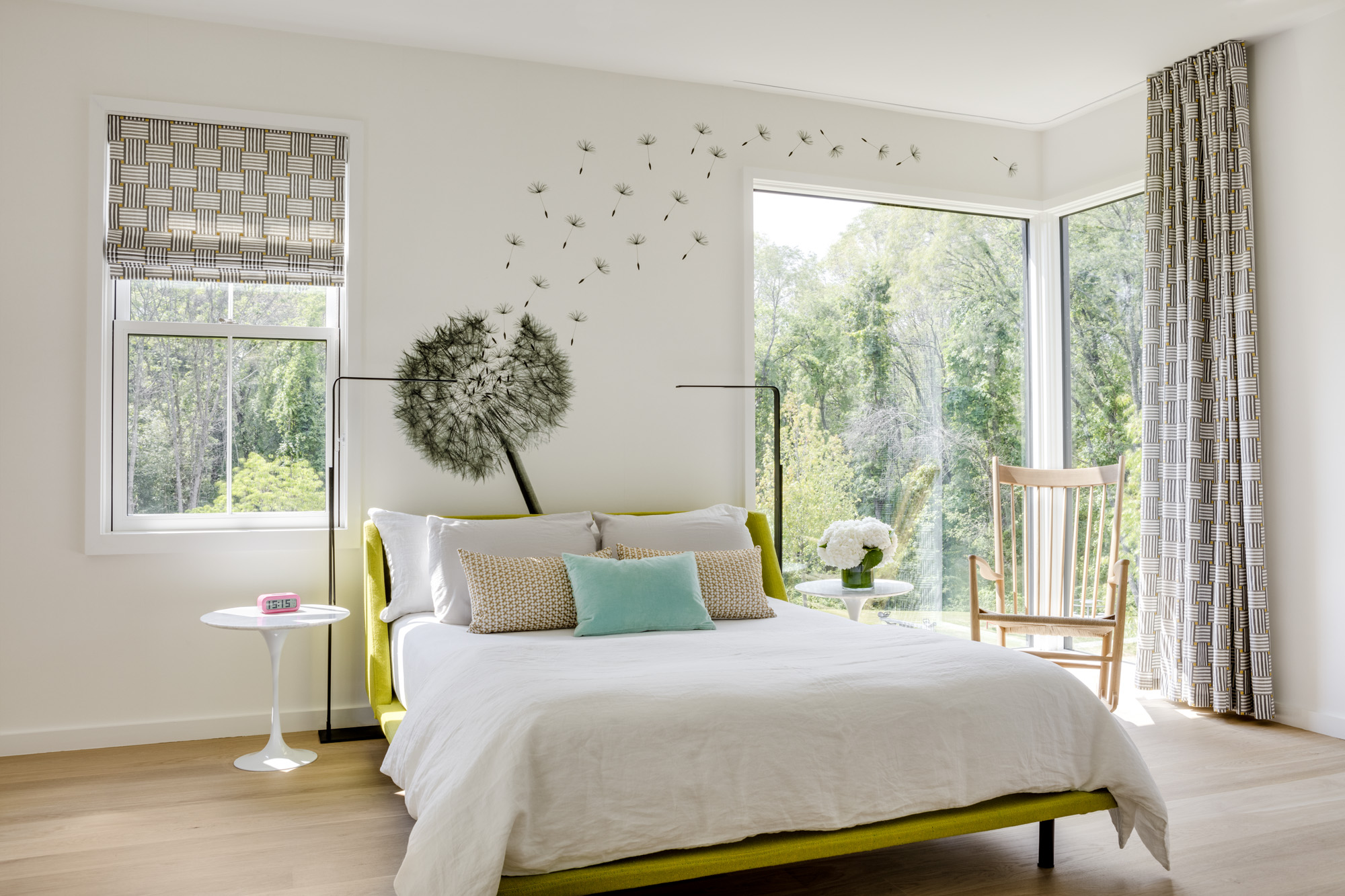 The second guest bedroom brims with natural light. Behind the Blu Dotbed, a dandelion decal from Wall &Decò serves as an artful wall accent. Matching printed shades and curtains from The Shade Store are a creative touch.