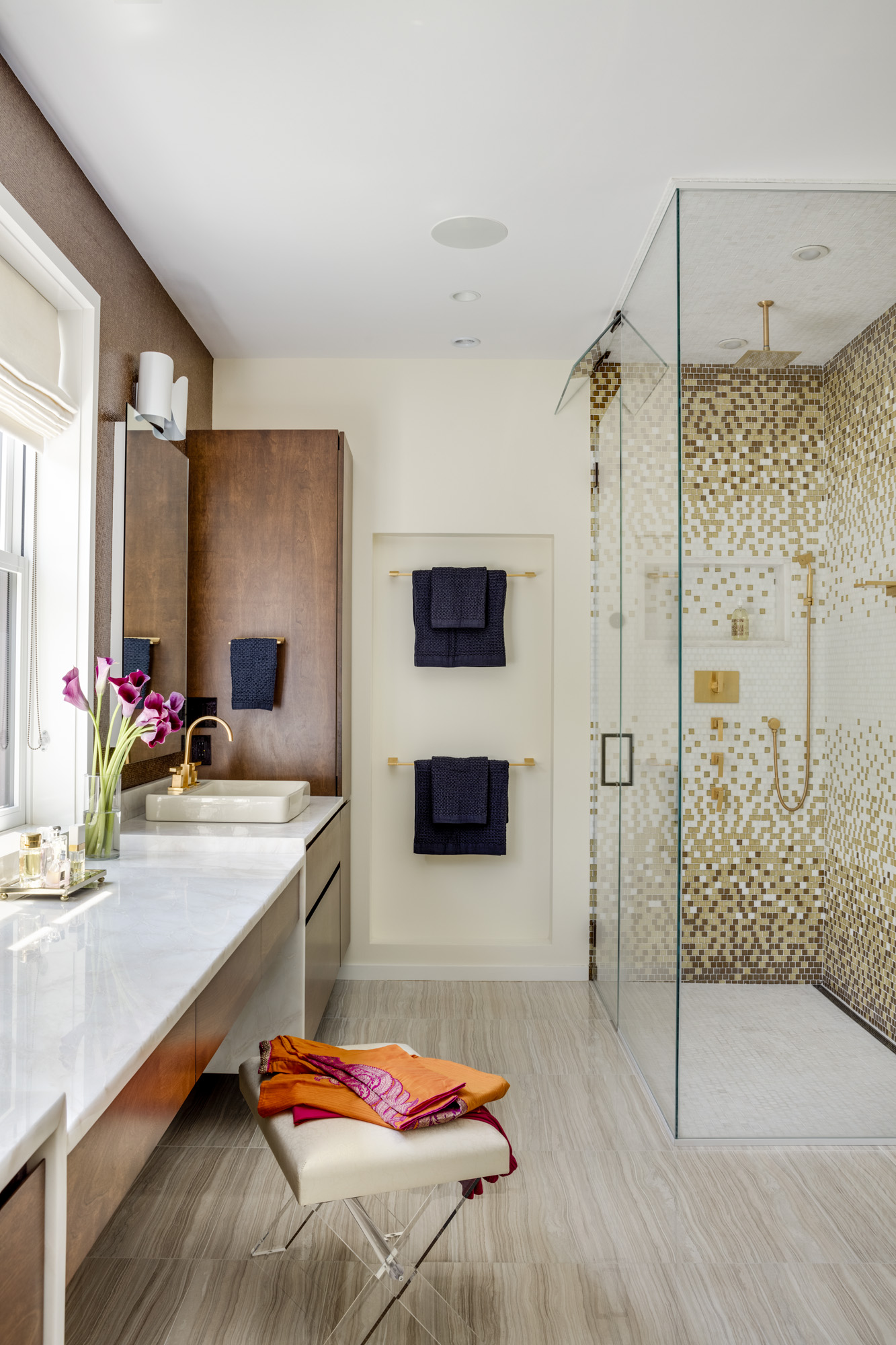 In the master bath, a glass mosaicfrom DiscoverTile provides visual interest; the floor and ceiling tile is also from DiscoverTile. Outside the shower, floor tile from Ann Sacks offsets the warmth of the built-in wood cabinetry and vanity with Calacatta marble from Athena Marble and Granite. The vesselsinks are byTOTO, while the faucet, showerhead, and handshower are from Newport Brass.