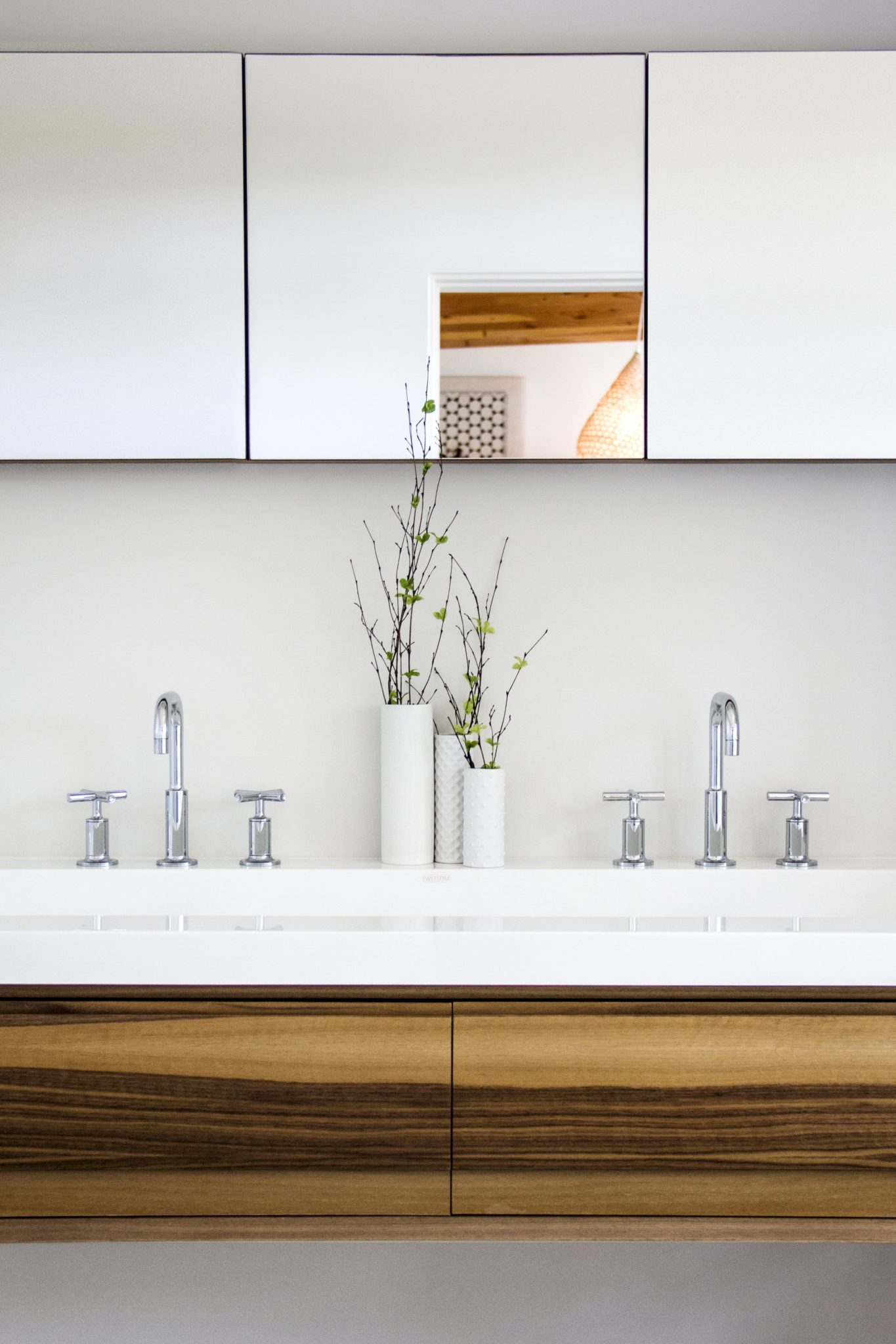 Kohler faucets and Wetstyle sinks serve as functionalaccents in the peaceful bathroom. Karma Dog Construction created the cabinetry and sourced the mirrors.