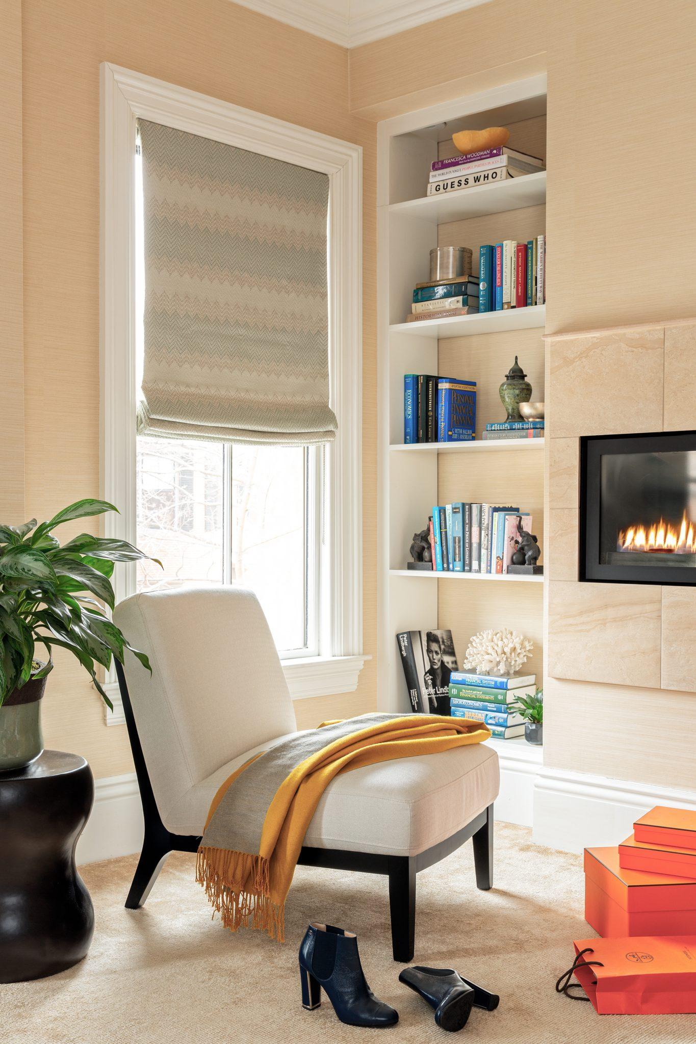 Minimalist seating space and miniature fireplace within cozy beige closet by Dane Austin Design