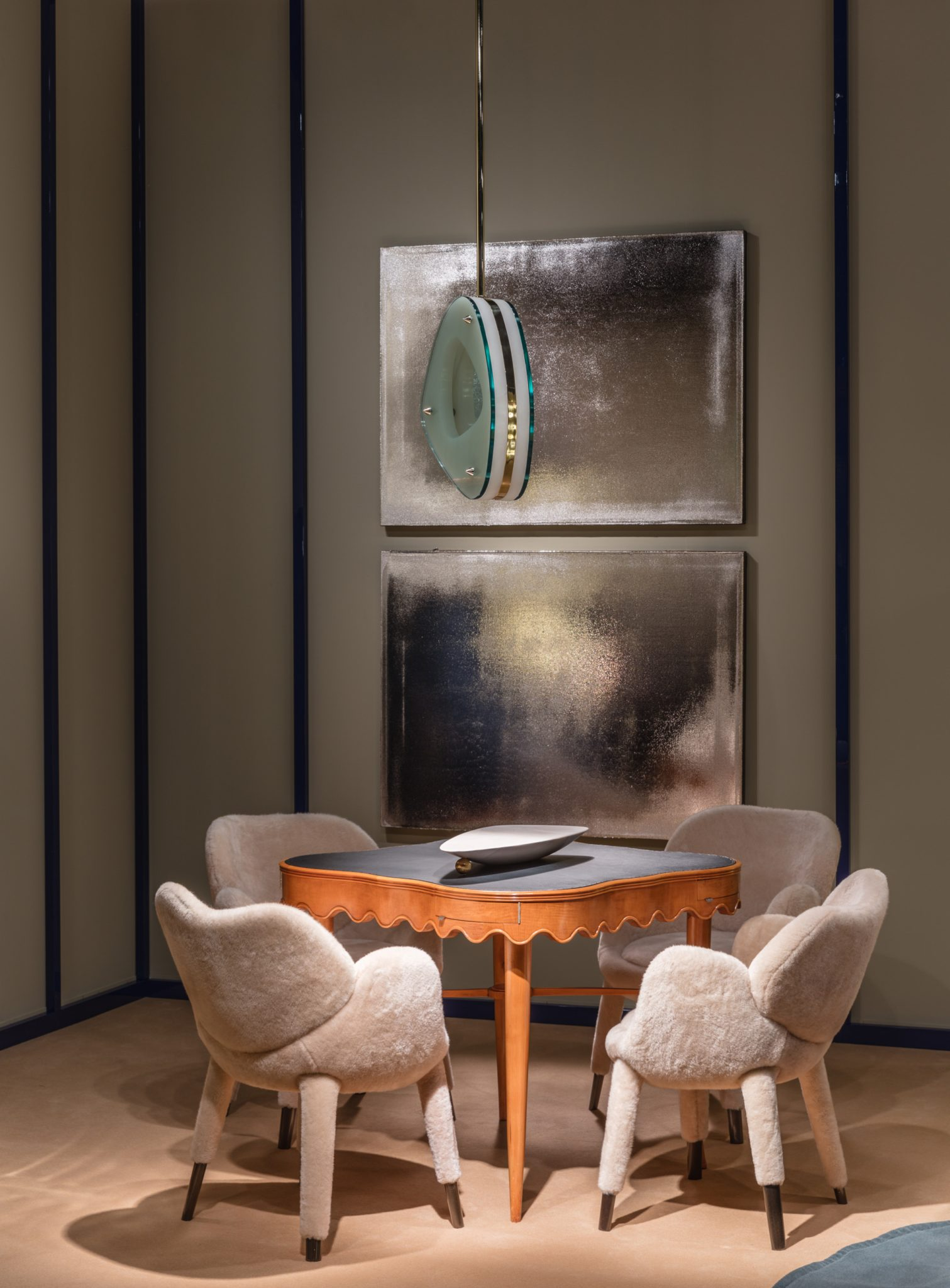 For a living room in Geneva, Salvagni paireda table by Paolo Buffa with four limited-editionFrangipane chairs and a Lens chandelier of his own design; theartwork is by Jacob Kassay.