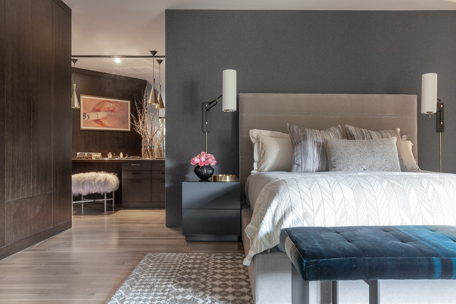 A Restoration Hardware bed frame is the centerpiece of the master bedroom.Winfield Thybony Design wallpaper brings a lush atmosphere to the room, while a patterned rug fromHaute Textile Flooring adds an extra dose of texture. Custom nightstands from Ciarlo Brothers stand guard on either side of the bed beneath sconces byAerin For Visual Comfort. To the left, the vanity area is visible, where a bench from Outpost Original offsets its wood surroundings.The bench at the foot of the bed was sourced from Lee Industries.