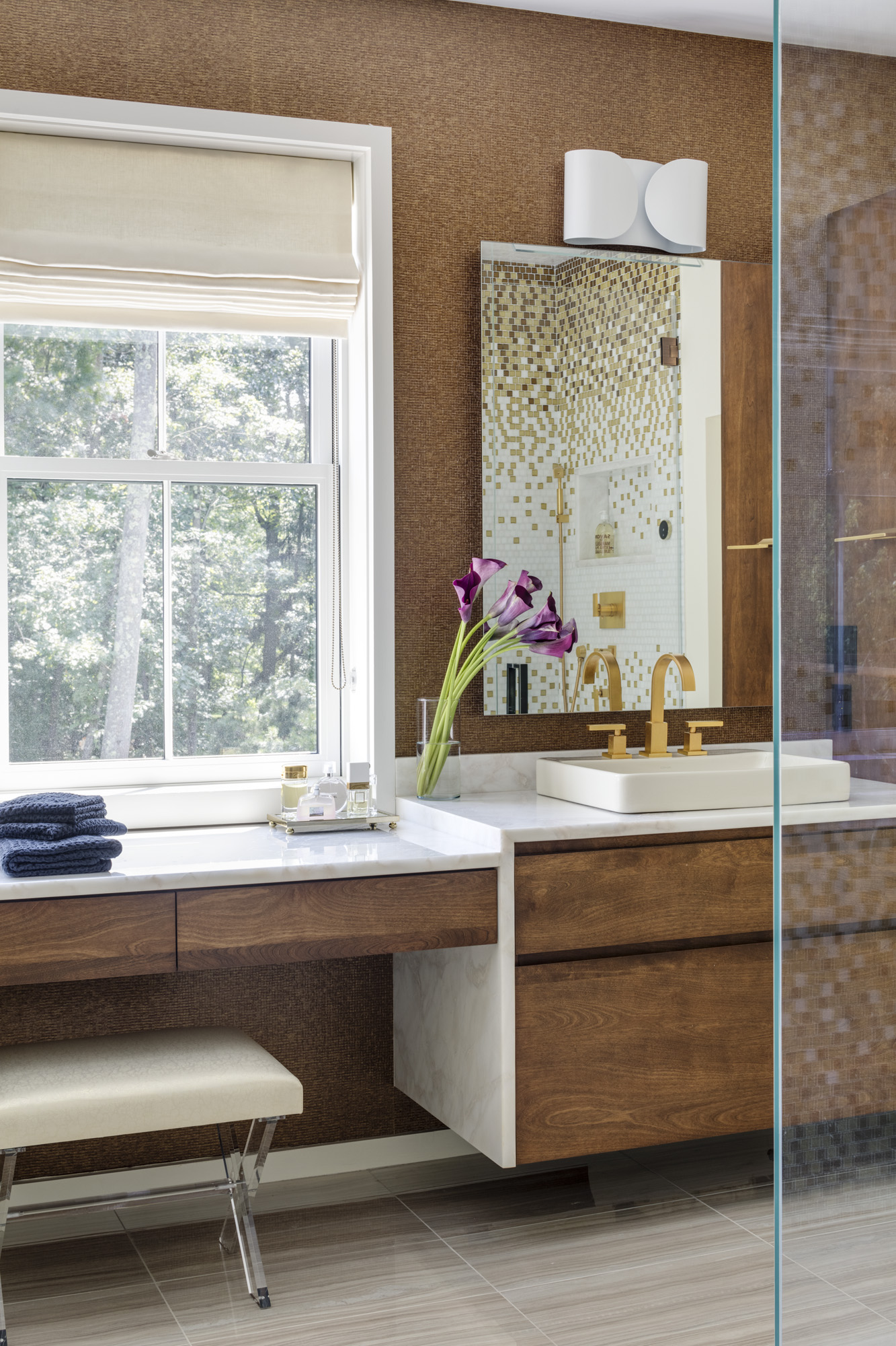 Patterned Élitis wallpaper complements the shower tile, reflected in the wallmirror. Chimera sconces are a fun, eclectic accent for the contemporary space.