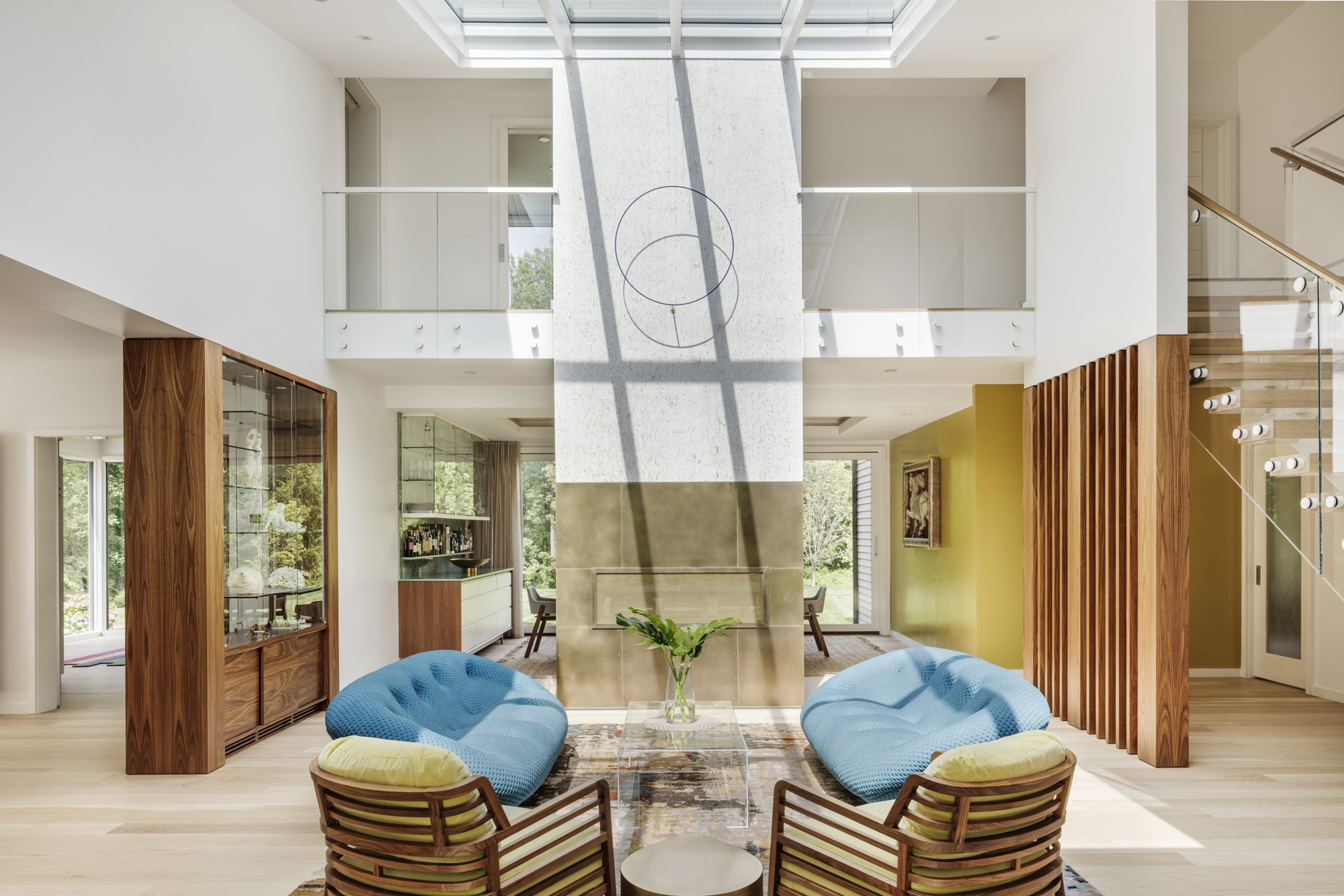 According to Vastu Shastra principles, the center of the design should be an open courtyard; however, given harsh New England winters, the designers chose to craft a large, openliving area with double-height ceilings and an expansive skylight instead. As one of the key aspects of Vastu Shastra is integration with nature, the skylight serves to enhance the connection between indoors and out, and between individual and nature. The wallpaper behind the fireplace is an Omexcofabric from Romo, while the cladding is from Make Architectural Metalworking. The modern fireplace is from Town and Country, and the circle light and coffee table are both from DDCNYC.