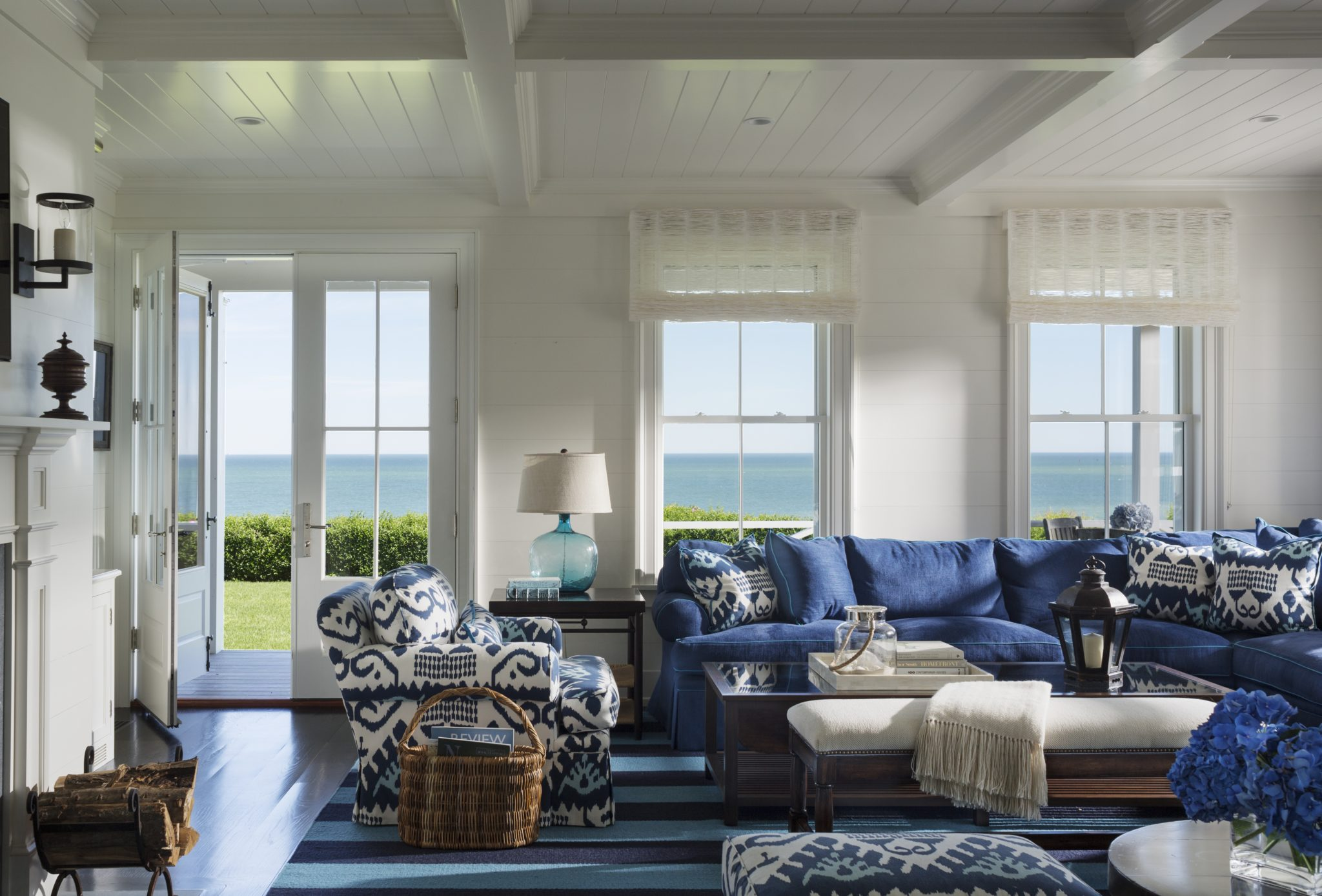 Spacious family room with blue and white ikat upholstery and crisp white walls by SLC Interiors