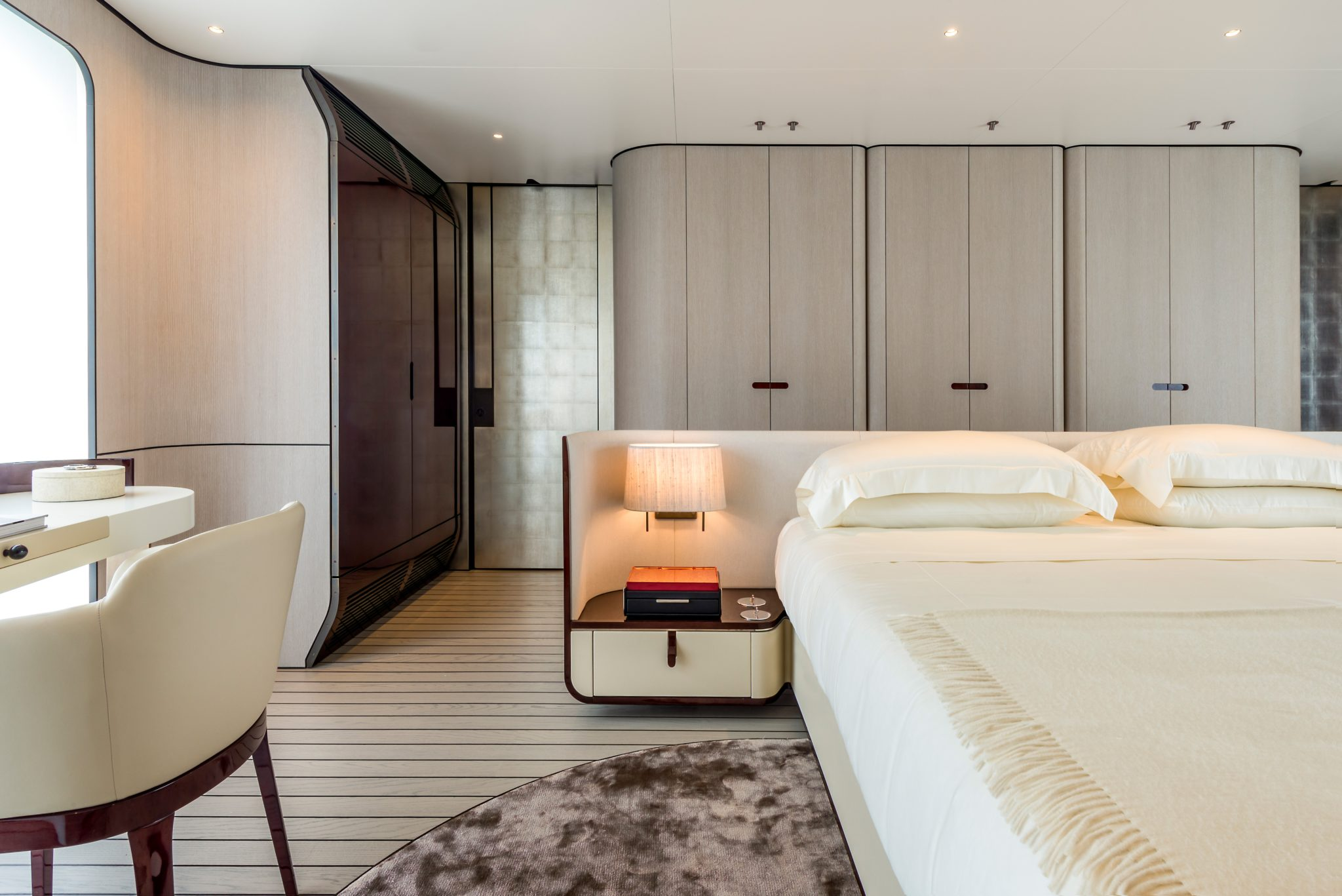 Yachts present special design challenges. To create warmth and volume in this floating bedroom, Salvagni designed a room of gentle curves, including a free-floating nightstand that is incorporated into the parchment-covered headboard.