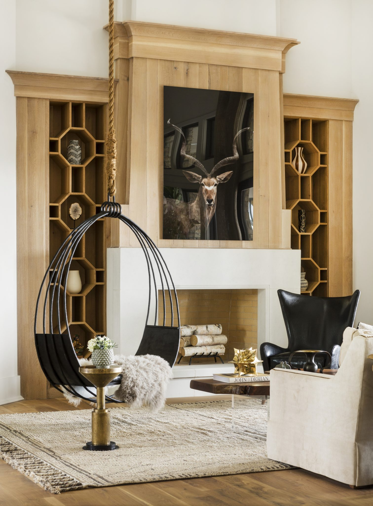 Horse Meadow country house featuring custom steel swing chair and intricate white oak bookcases. by Casey Sarkin Interior Design, Luna Inc.