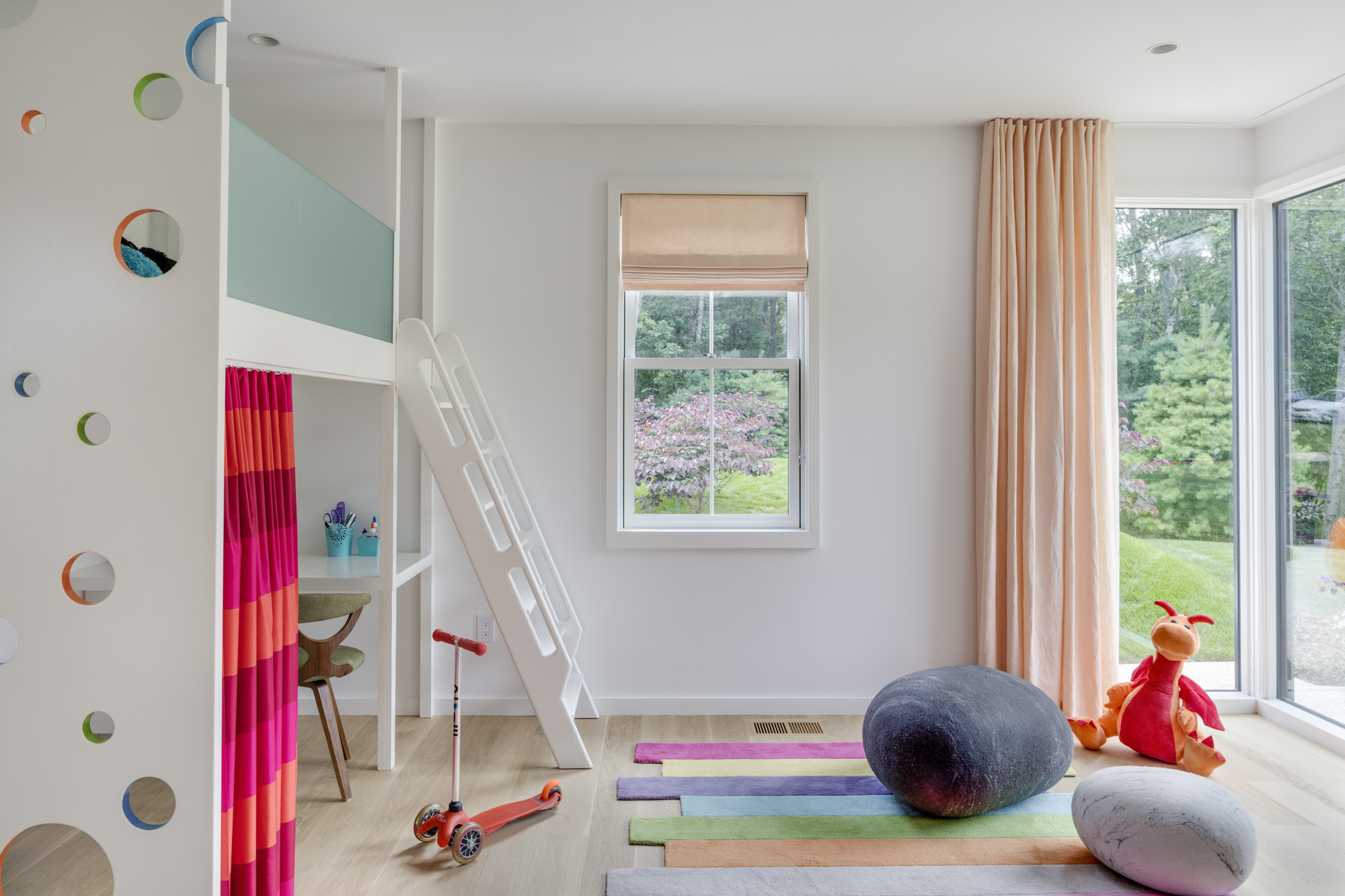 Stripes and rich colors, paired with bright white walls,make for a calming, whimsical playroom. The matching peach shades and curtains are from The Shade Store.