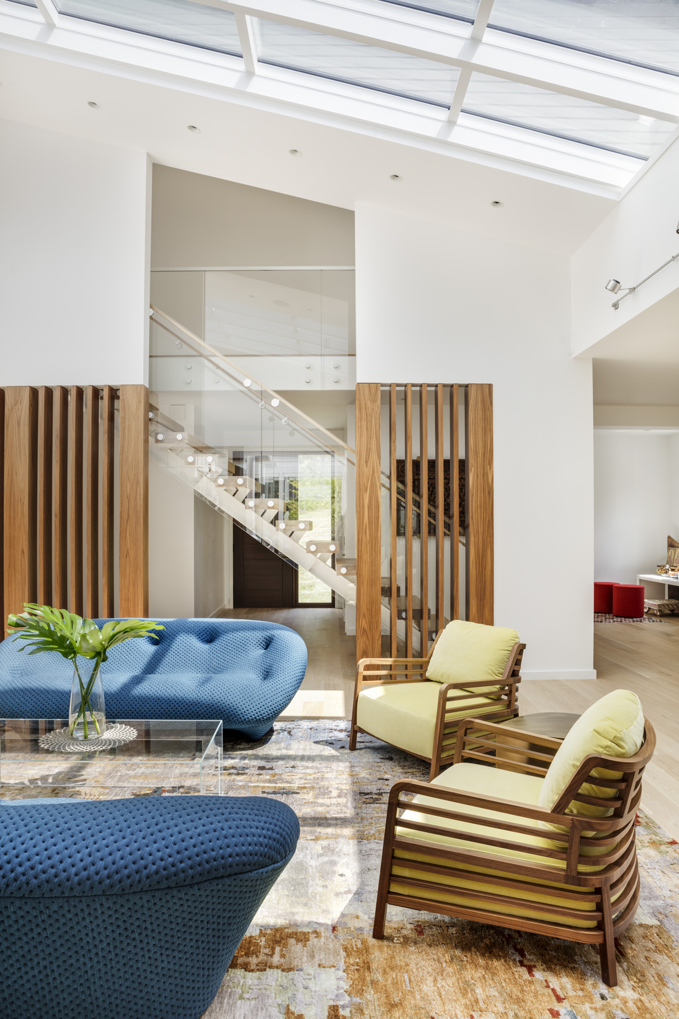The architecture of the living room features a largeskylight andbuilt-in wood screen. Blue Ligne Roset sofas are starkly contemporary, while the frames of the Ligne Rosetarmchair match the screen. The brass table between the chairs is from Jonathan Adler.