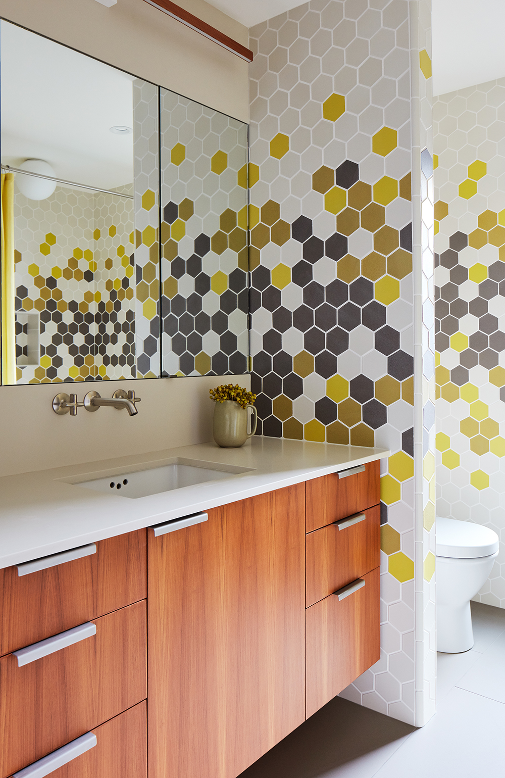 The son shares the guest bedroom with any visitors, and it imitates the cheerful patterns of his room with a hexagonal tile from Heath Ceramics.