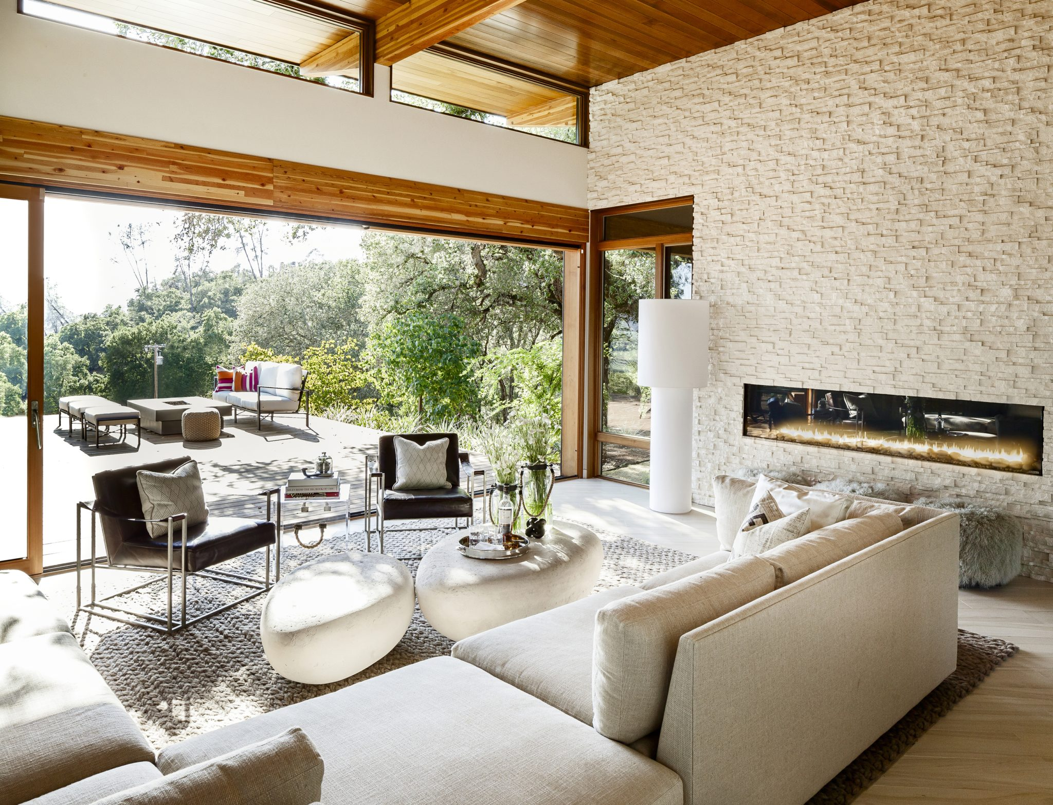 A long, cream-colored sectional from Mitchell Gold + Bob Williamsand modernistBernhardt armchairsprovideample seating in the living room. Thetaupe rug from Cabana Home adds another lay of texture to the space, as does a detailed tile layout from Ceramic Tile Designthat surrounds the fireplace.Near the fireplace, theMongolian wool stoolsare fromPfeifer Studio, and the stone coffee tables are from Phillips Collection. The white, contemporary floor lamp from Foscarini brings in an avant-garde note to the overall design.