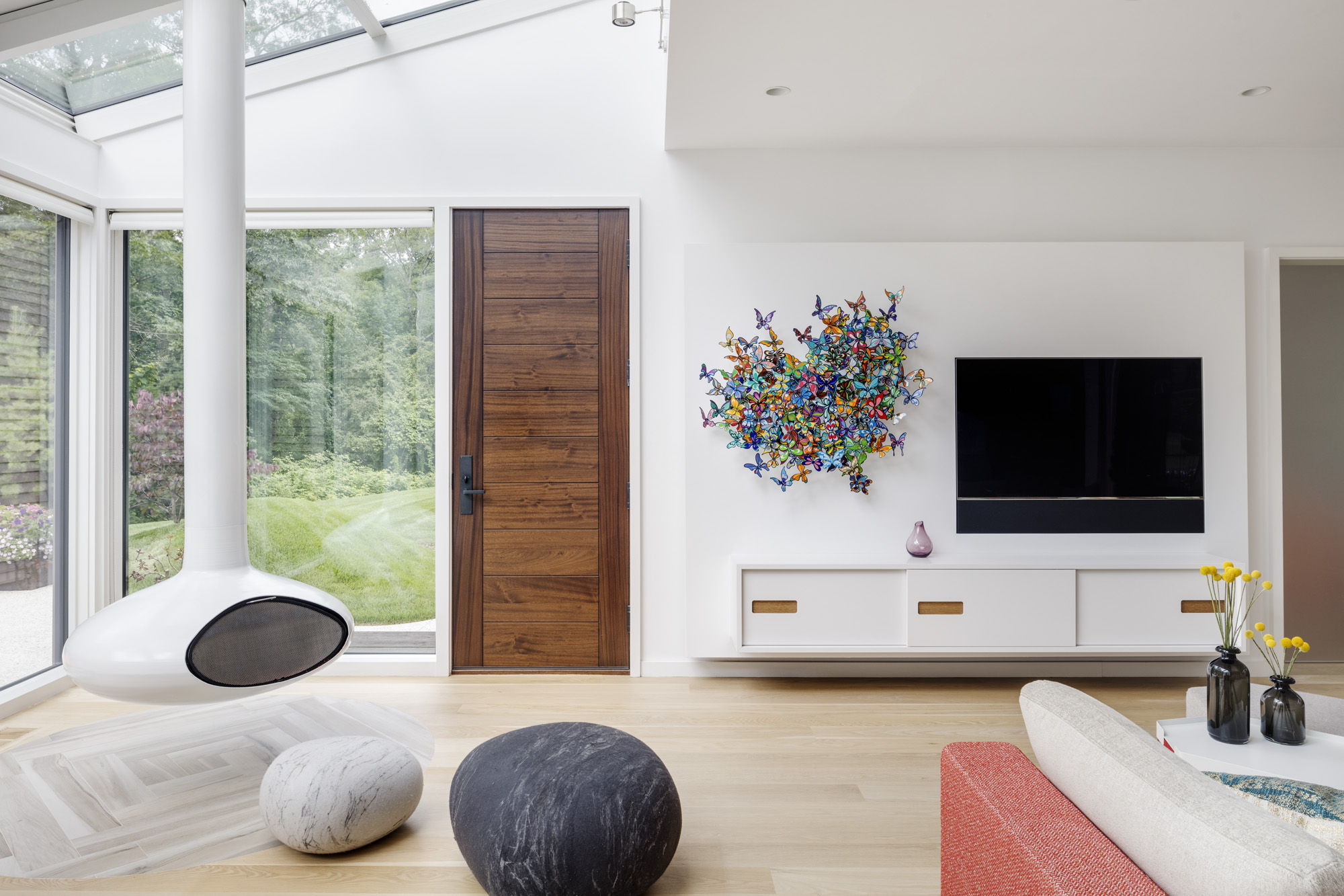 Matched with white walls, the white oak floors throughout the house set a neutral backdrop for playful, colored accents and accessories. In the family room, the white console from Asplund is placed below the bright butterfly artwork byDavid Kracov, titled My Heart is All A Flutter.