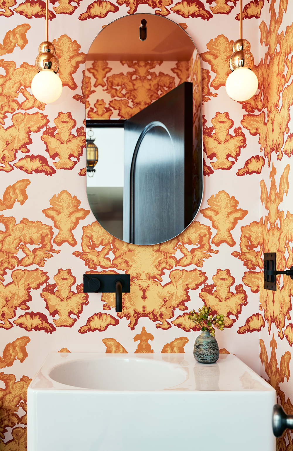 Located near the kitchen, the powder room features a hypnotic, hand-printed wallpaper by Timorous Beasties that's playful and electric. Ball light pendants by Michael Anastassiades enhance the Mod ambience.  The curve of the mirror mimics the arch shape throughout the house. In many rooms of the house, the design team used Invisible Lightswitches from Forbes & Lomax so as not to interrupt the flow of the wallpaper or paint.