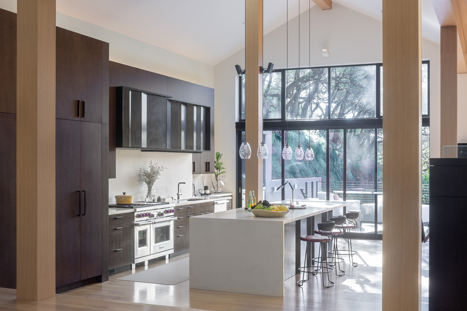 To the side of the dining room, the kitchen sits beneath an A-frame ceiling. Leather barstools from McGuire Furniture line the minimalist island. Suspended hand-blown lights from Hennepin Made add a touch of softness to the heft and scale of the design.