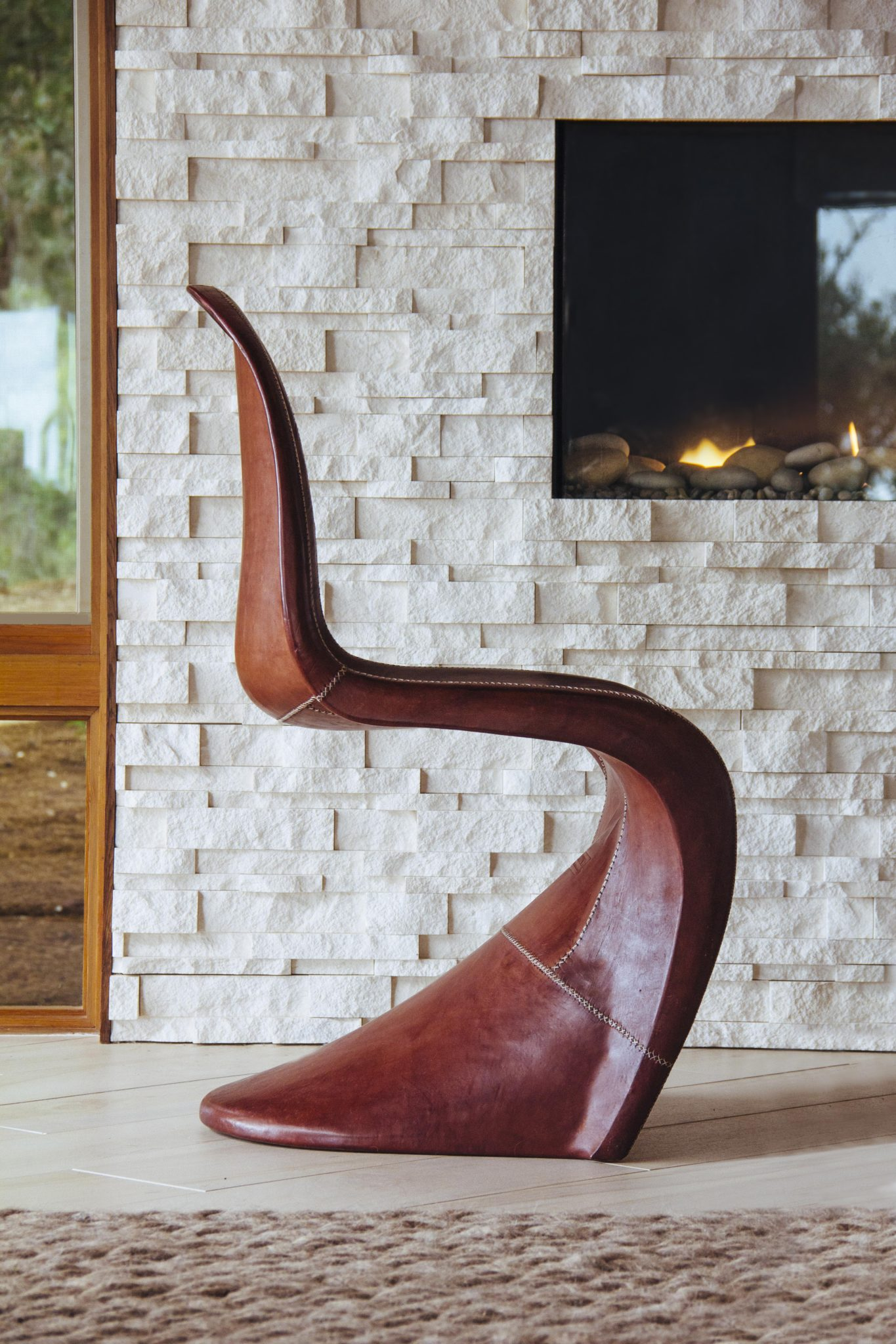 The curved leather chair is from Jayson Home.