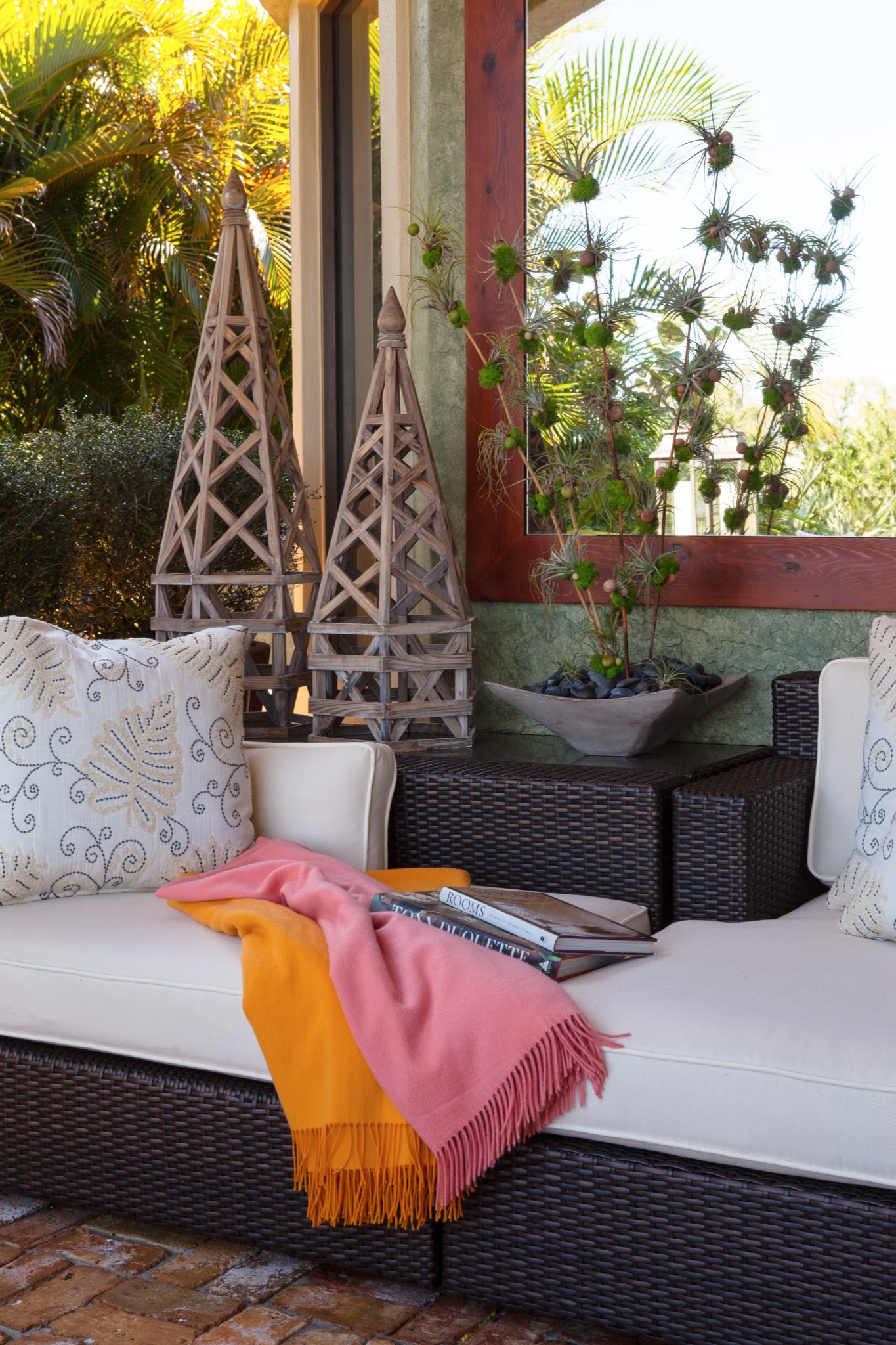 A cozy white cushioned rattan sofa for a relaxing read. by Gil Walsh Interiors