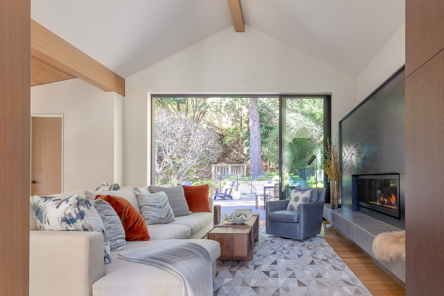 Beside the kitchen, the living room opens up to a comfortable porch. A floor lamp from Arteriors offers light to a leather chair from Lee Industries;at an angle, the chair faces a soft sectional from Camerich. The coffee table is from Fourhands.