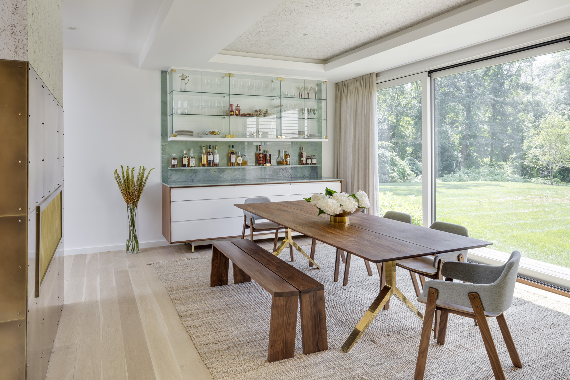 A walnut dining table from DDCNYC, along with a long bench and set of chairs from Blu Dot, lay the foundation for a rustic minimalist aesthetic in the dining room. Above the table, the ceiling is covered in a texturedOmexcowallcovering fromRomo, and behind the bar, a chic, reflective backsplash fromAthena Marble and Granite offers a hint of gloss.