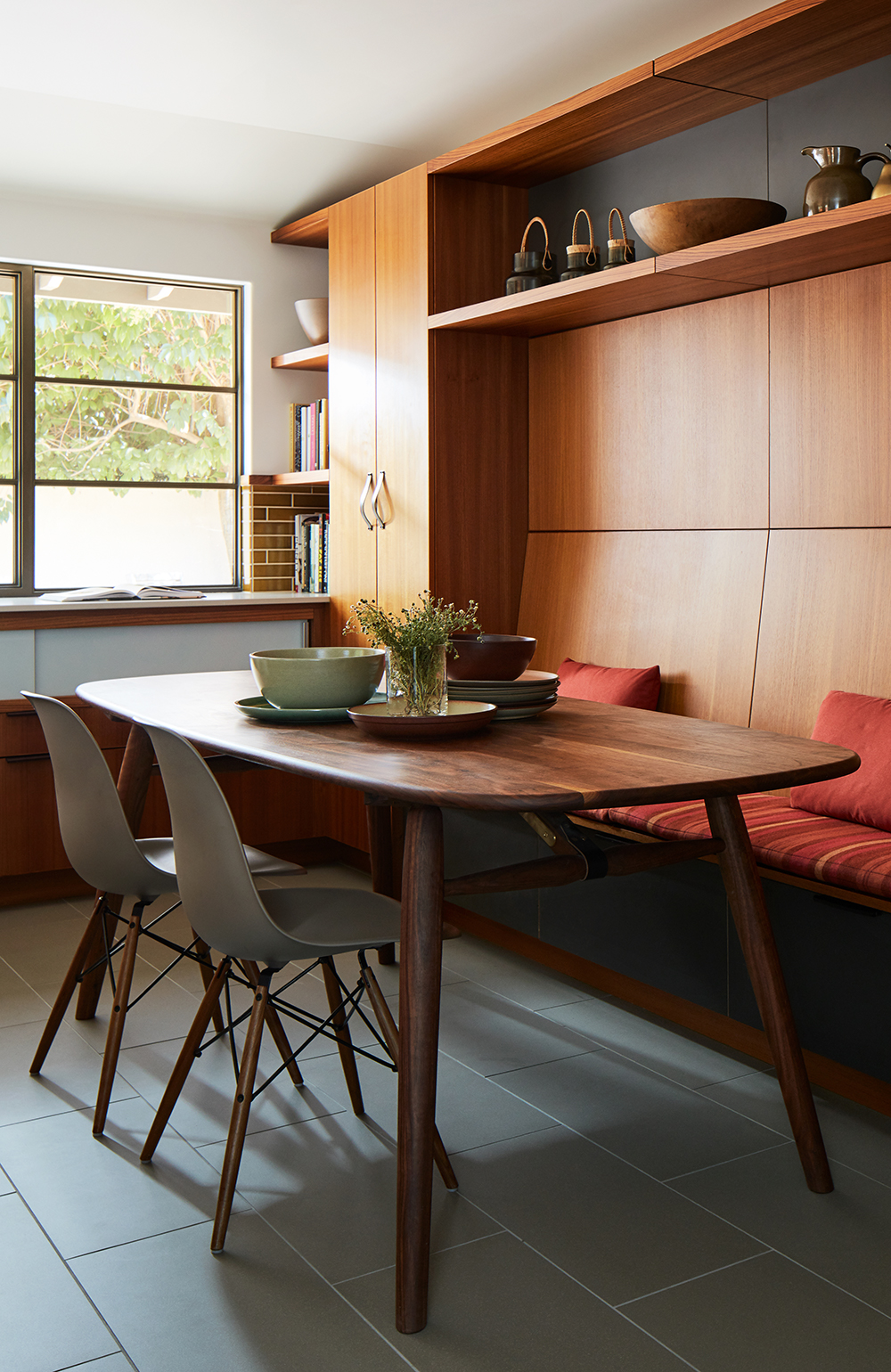 This informal dining table was made custom by Jacob May, and the custom, built-in bench was upholstered in a rich striped fabric from from Knoll.