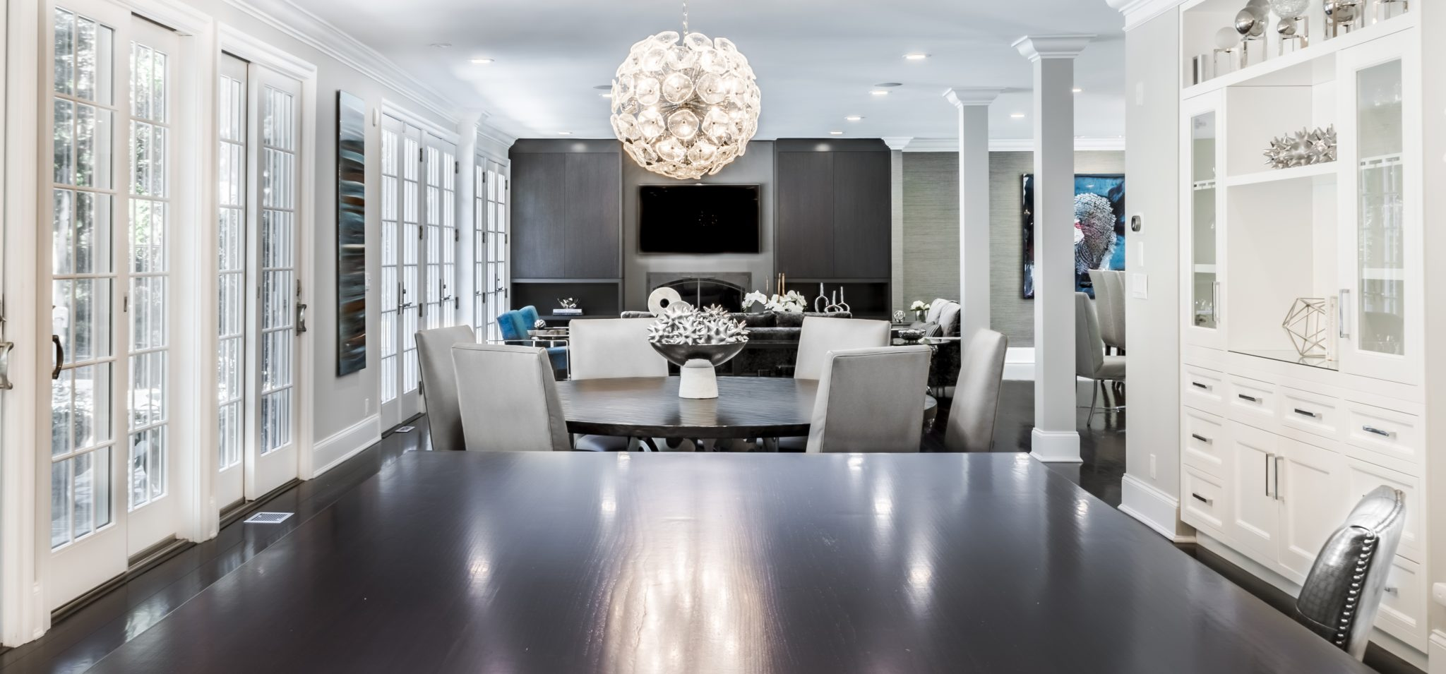 Open concept kitchen into living room with wall of sliders by Kim Radovich Interiors