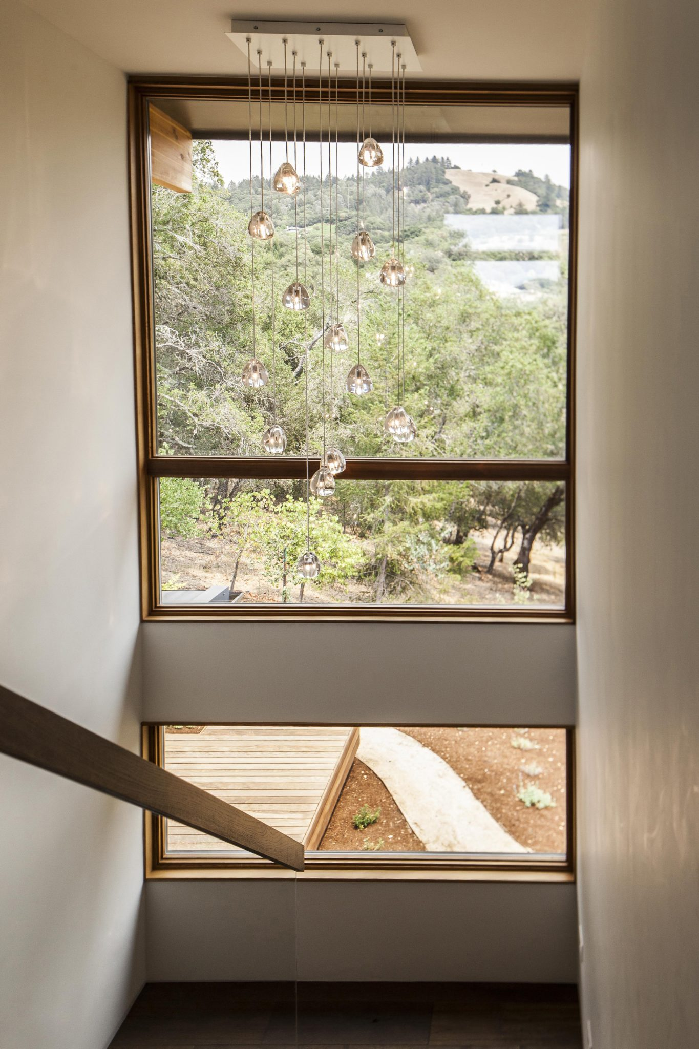Framed against the landscape through the window behind it, thisMizu15-light pendant from Terzanidecorates the staircase.
