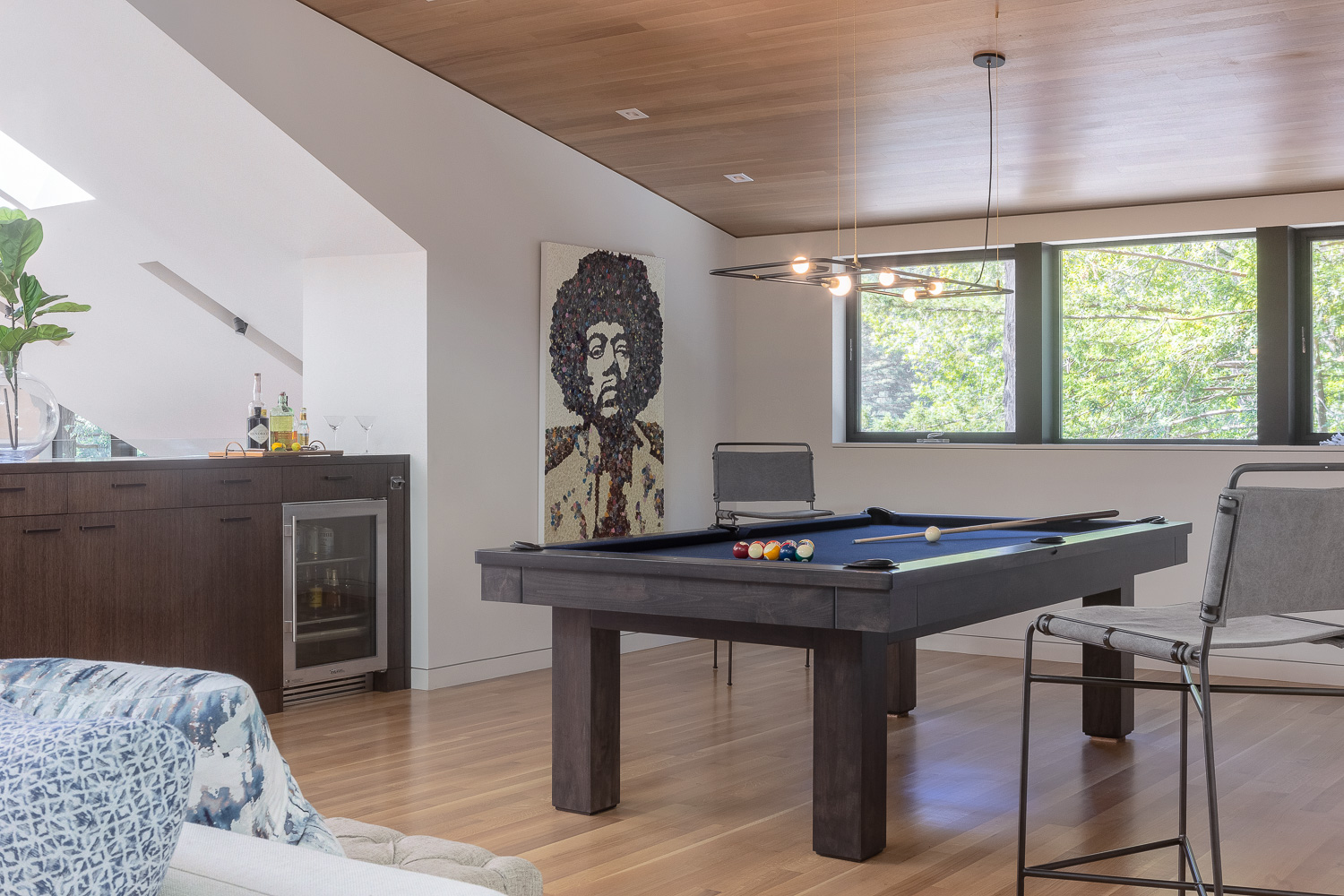 Behind the sectional sits a pool table, decorated with lights from Lambert et Fils. Calabrese custom designed the pool table to suit the room; often, houses in the Bay Area don't have pool tables because they're constrained by space, she notes. The bar stools are from Fourhands.