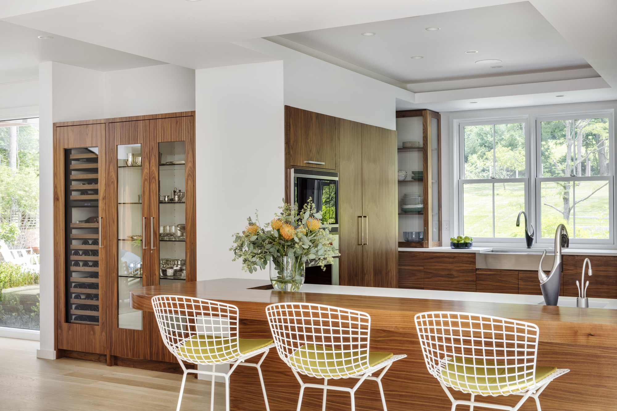 White Knoll chairs with a woven metal design are juxtaposed against the polished look of the rest of the kitchen. The wine refrigerator is from Sub-Zero.