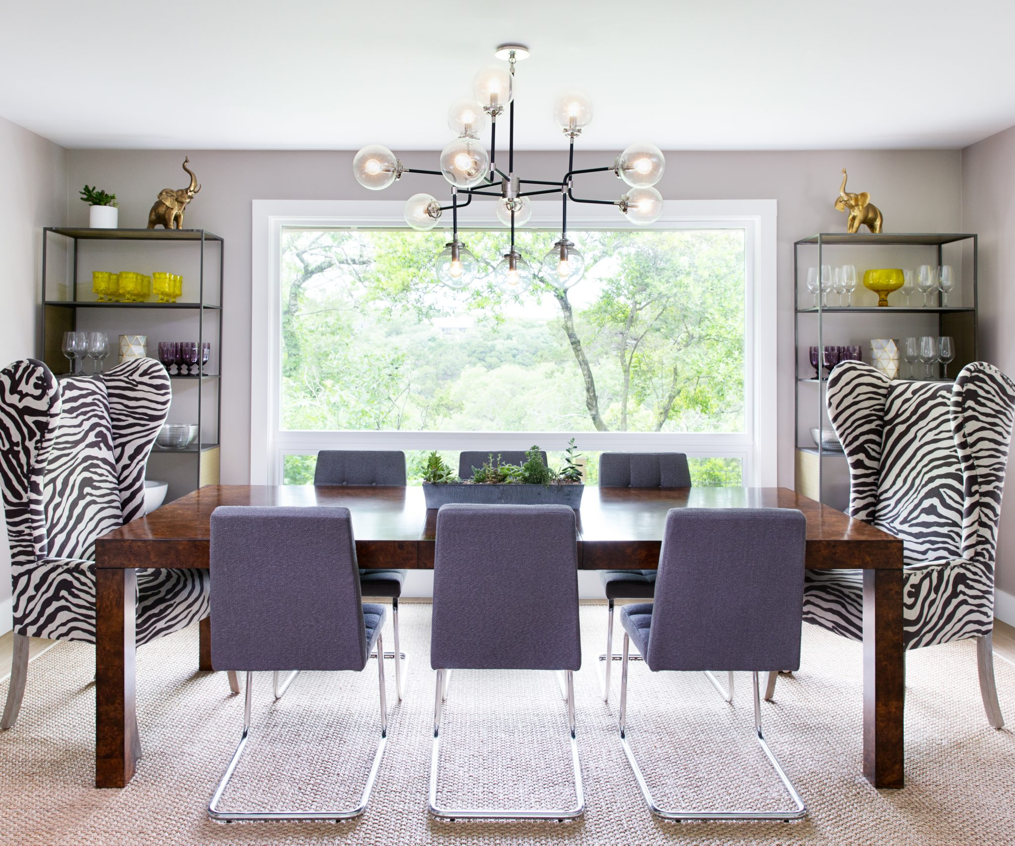 """9. Mix & Match   Mix and match furnishings, lighting, or artwork to give your space a creative style. """"Mismatched furniture just makes everything better,"""" says Fisher. """"It's less expected and creates interest, especially when the patterns are so different."""" In this space, six neutral dining chairs are contrasted by two zebra print armchairs."""