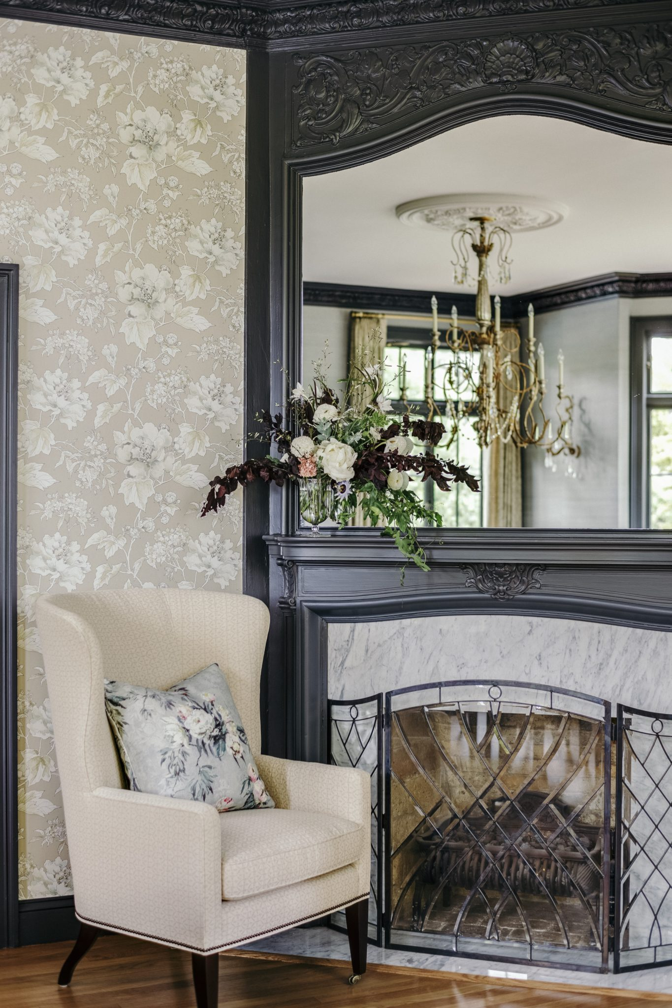 Reflected in the mirror, the 12-light crystal chandelier is from Horchow, and the wing chair is from Baker Furniture.