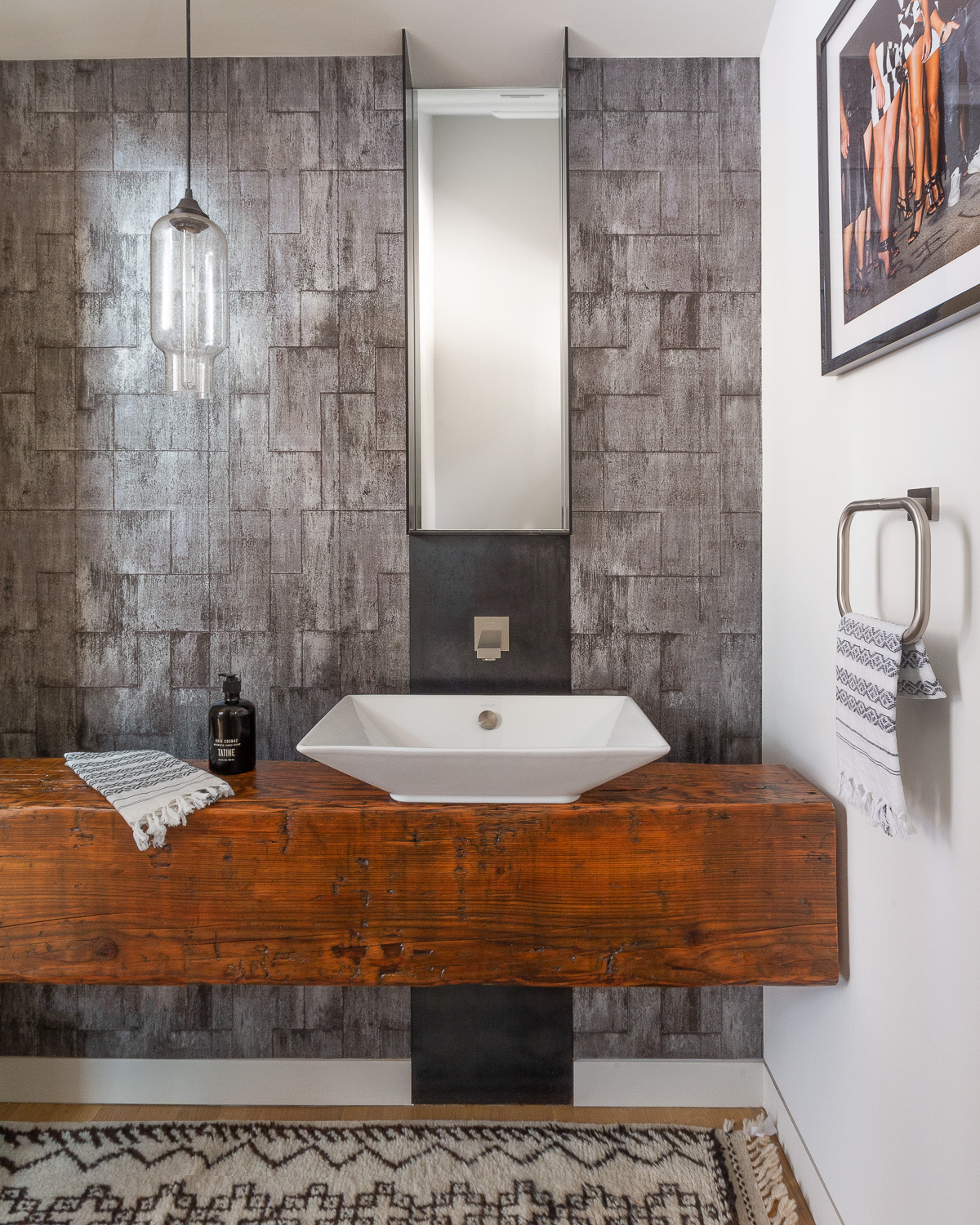 Off the pool room, a luxurious powder room is enhanced by a reflective Elitis wallcovering. The area rug is from Tazi Designs, and the pendant light is from Nicheliving.