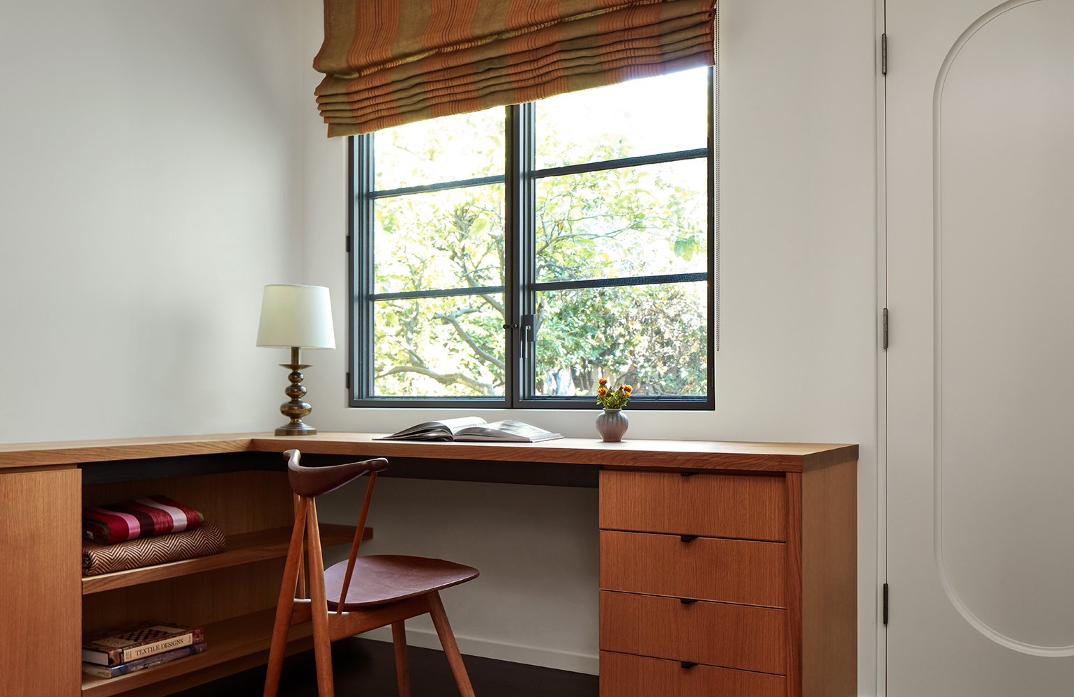 The first-floor home office includes a laundry area, and it can be transformed into a guest room if necessary. The Swedish flatweave rug is vintage from FJ Hakimian, and the window shade fabric is from Osborne & Little.