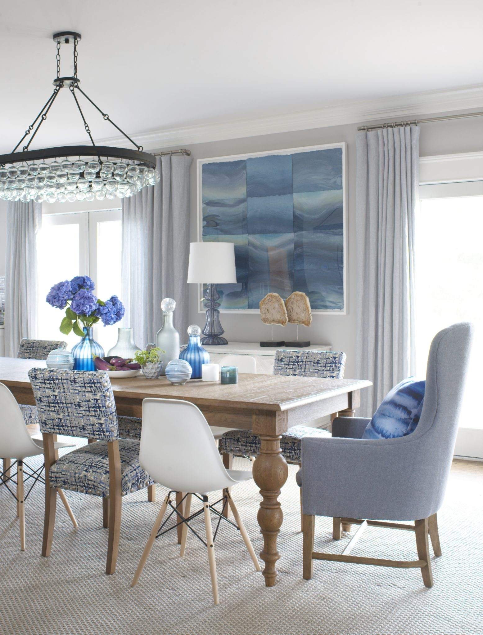 """7.Emphasize Views with Every Detail   If a home has water views, every detail in the house should enhance those vistas, rather than obstruct them. Window treatments are key for emphasizing water views, and designers often recommend sheer or light drapery. Other accents matter as well.For example, large, contemporary pendants may help a room look more modern, butthey risk blocking windows from different perspectives in a room, depending on the layout of a room and the fixture's location.Rachel Reider, a Boston-based interior designer, recommends glass lighting.""""Glass oversized light fixtures are another go to element in creating a modern coastal environment,"""" says Reider. """"They make a statement without obstructing water views."""""""