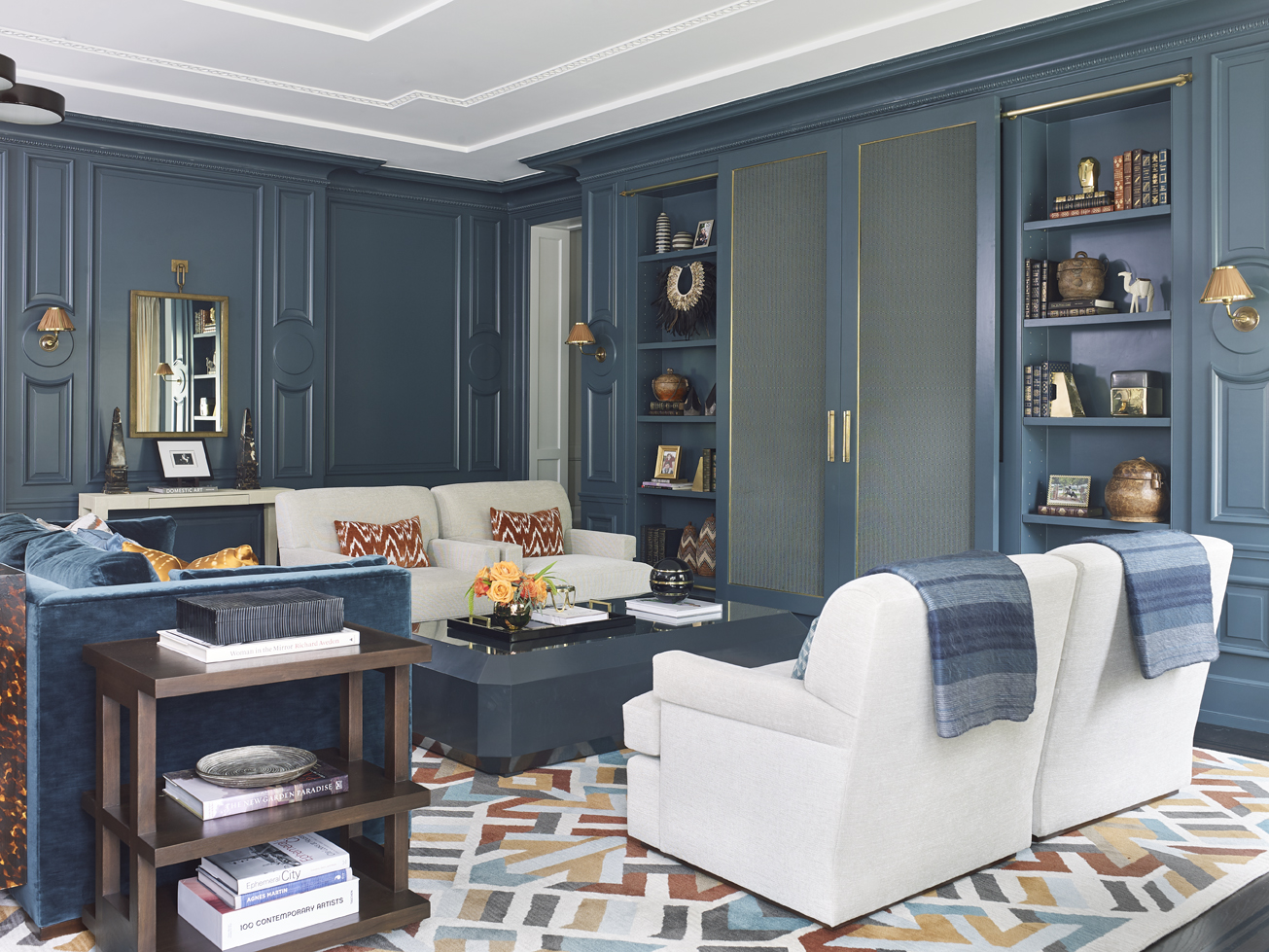 The boiserie was inspired by the Petit Trianon in Versailles, which was built a century after the Grand Trianon during the transition from the Recoco to Neoclassical period in France; sliding media doors stylishly obscure electronic equipment.