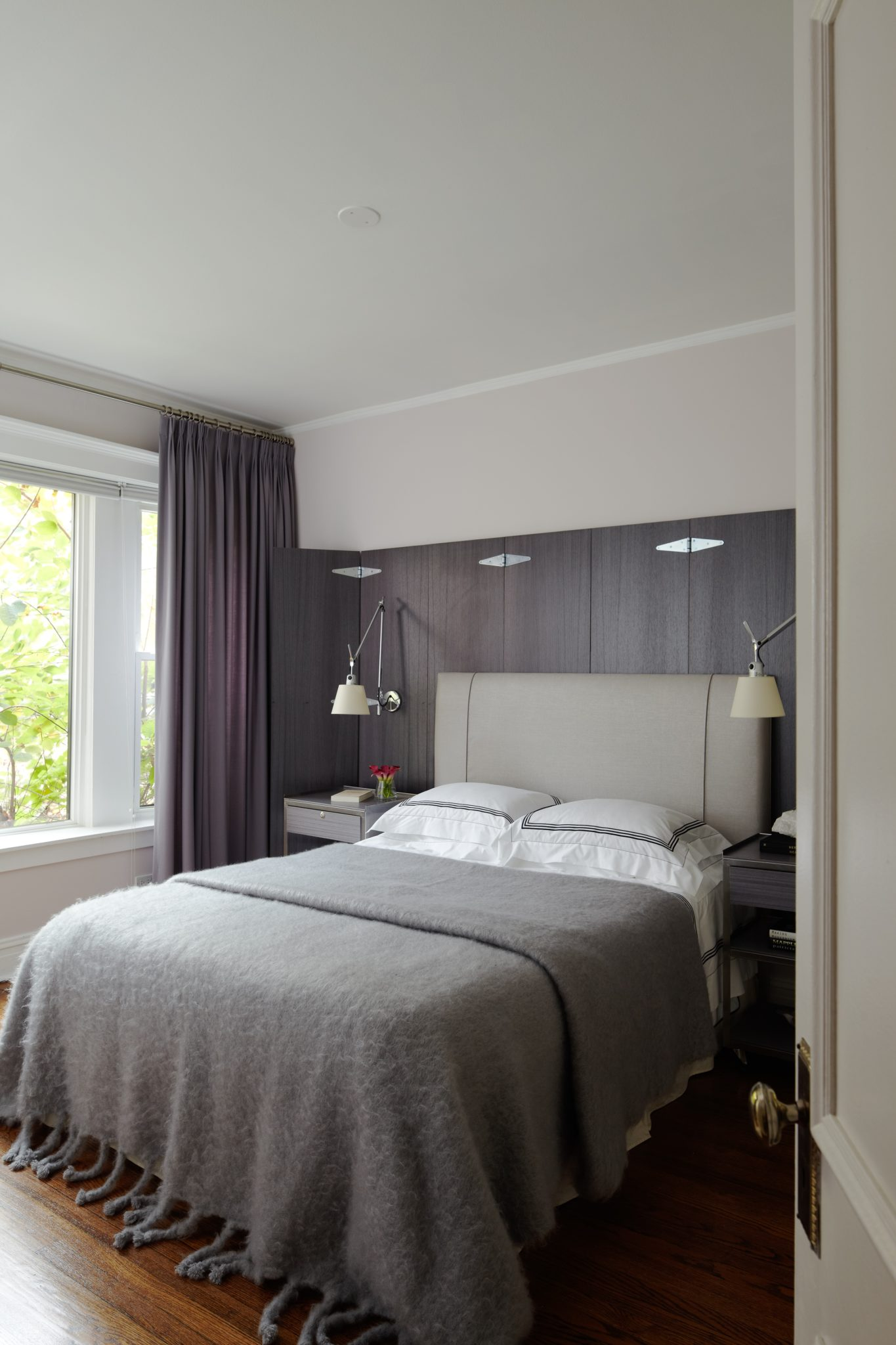 The bedroom has a bespoke screen behind the bed which also envelops the night tables. The sheets on the bed are Pratesi and the blanket is Hermès.