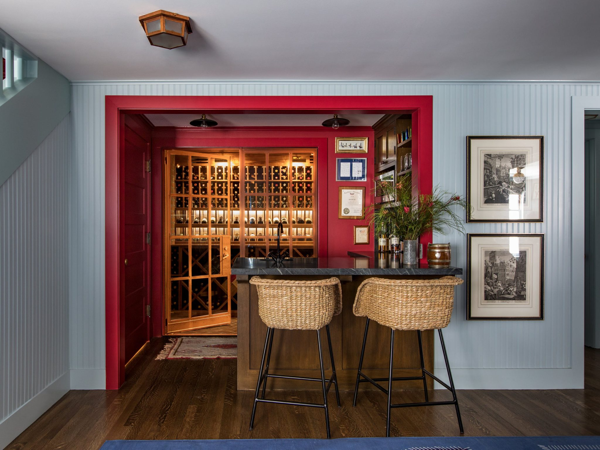 """Be Daring. """"A basement bar is a perfect opportunity to be bold and daring, and to color outside the lines,"""" says Tim Barber. """"We want guests to see the bar and be energized by thoughts of the fun evening to come.""""   Located a few steps above the media room, this space was designed to feel a bit like a snack bar in a 20th-century cinema."""