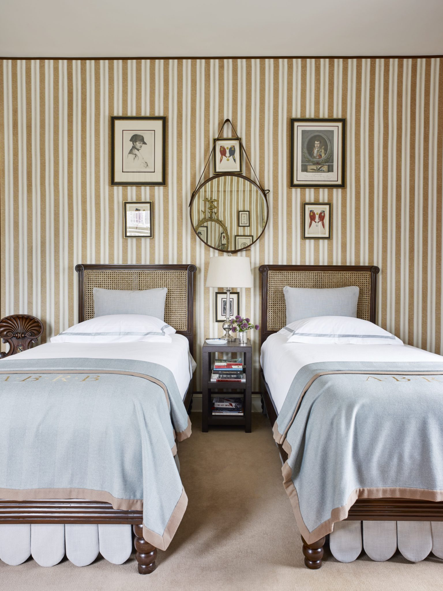 The guest room of a Fifth Avenue apartment designed for long-time clients houses a collection of Napoleon memorabilia and evokes traditional campaign style. The embroidered cashmere throws on the beds are from Loro Piana.