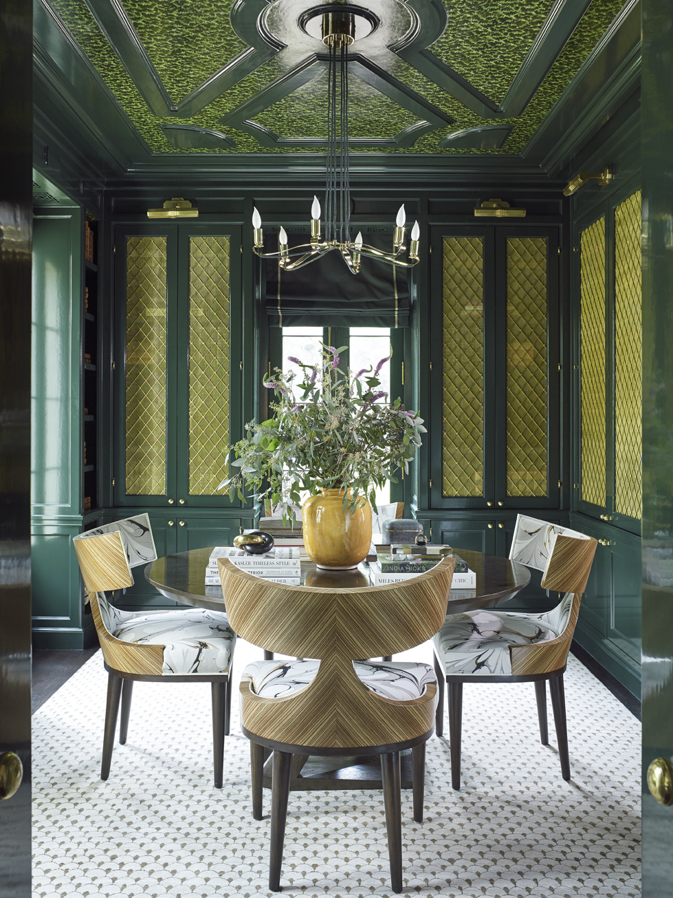 Deep emerald green with a touch of cyanbrings an indulgent, maximalist tone to the library. Lacquered walls and mouldings surround the room, punctuated by glass cabinet doors featuring unique metalwork.