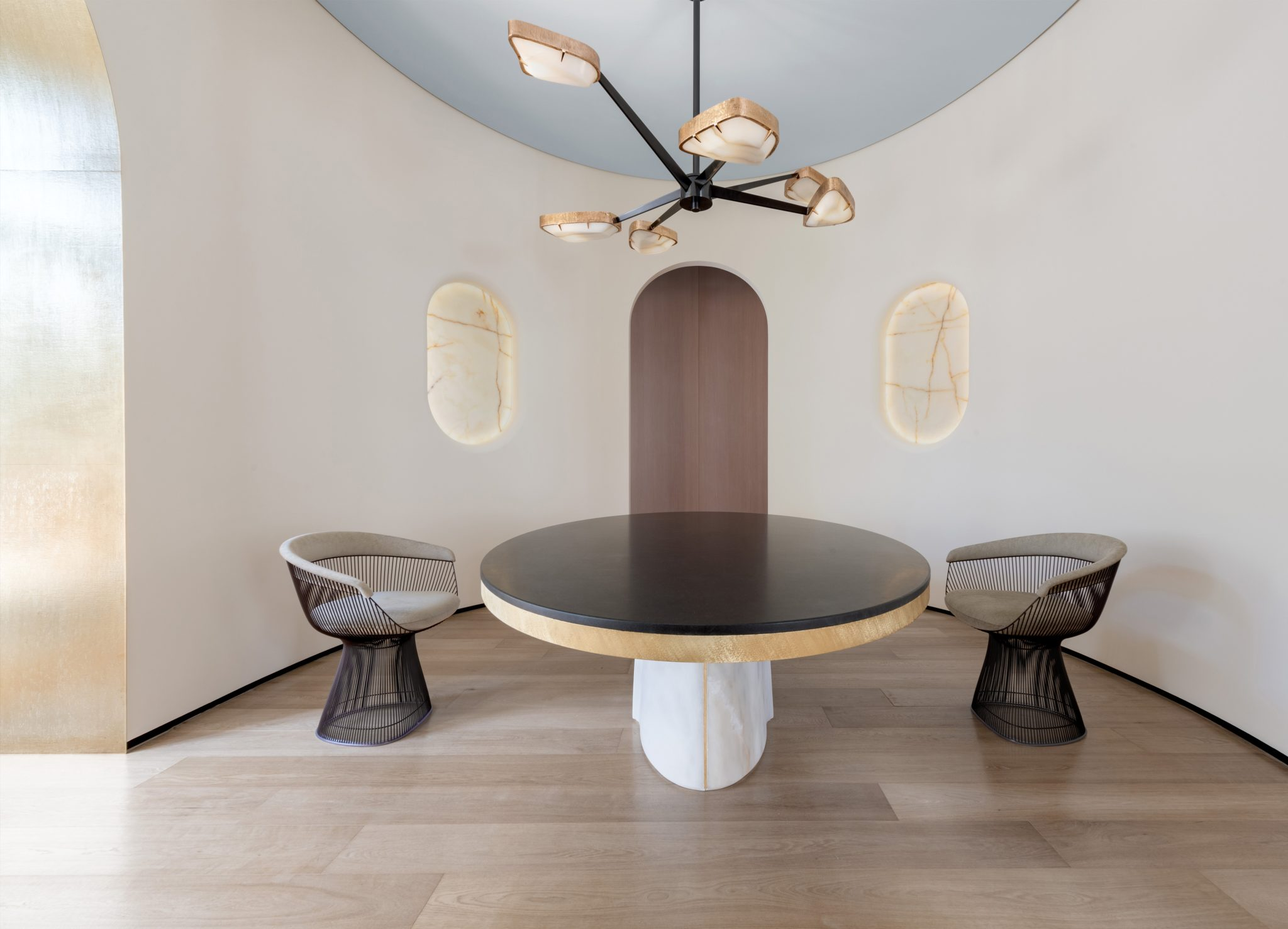 An oval dining room in Rome features vintage Warren Platner dining chairs arounda custom table, a black-lacquered Spider chandelier, and recessed onyx wall lights; the archways arelined in bronze toadd subtleglamour.