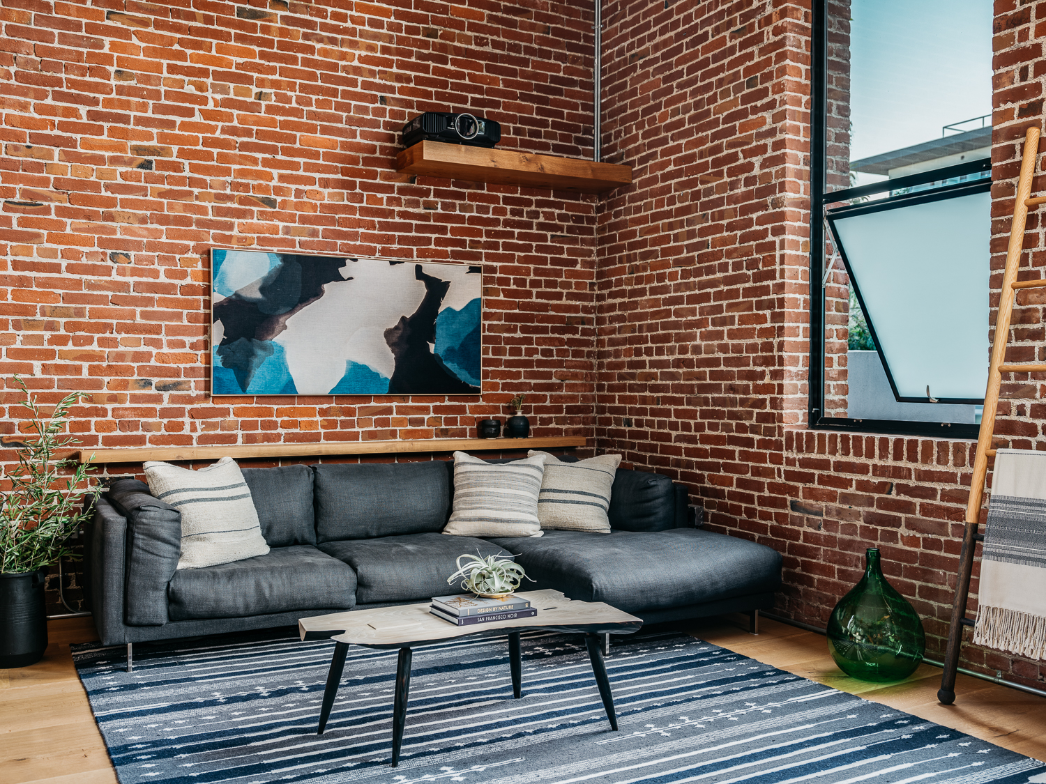 """Display Oversized Artwork   Oversized artwork can help balance the scale of an industrial space, while also adding personality and warmth to the interior. """"Art is a key component to adding that final touch of personalization to any space,"""" says Gretchen Murdock, founder and design director of MODTAGE Design. """"It makes the space unique to the client and helps to create focal points to lead the eye. I always find that in looking at someone's art, you are able to learn a little more about that person.""""  """"Smaller pieces of art can get lost on those large lofty walls,"""" adds Lagrange, who also uses framed pieces of wallpaper or textiles in place of large artwork."""