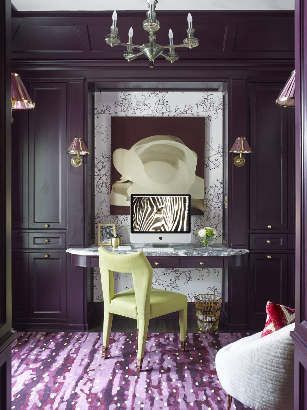 Built-in cabinetry in eggplant-colored paintmakes the home office stylish and organized.