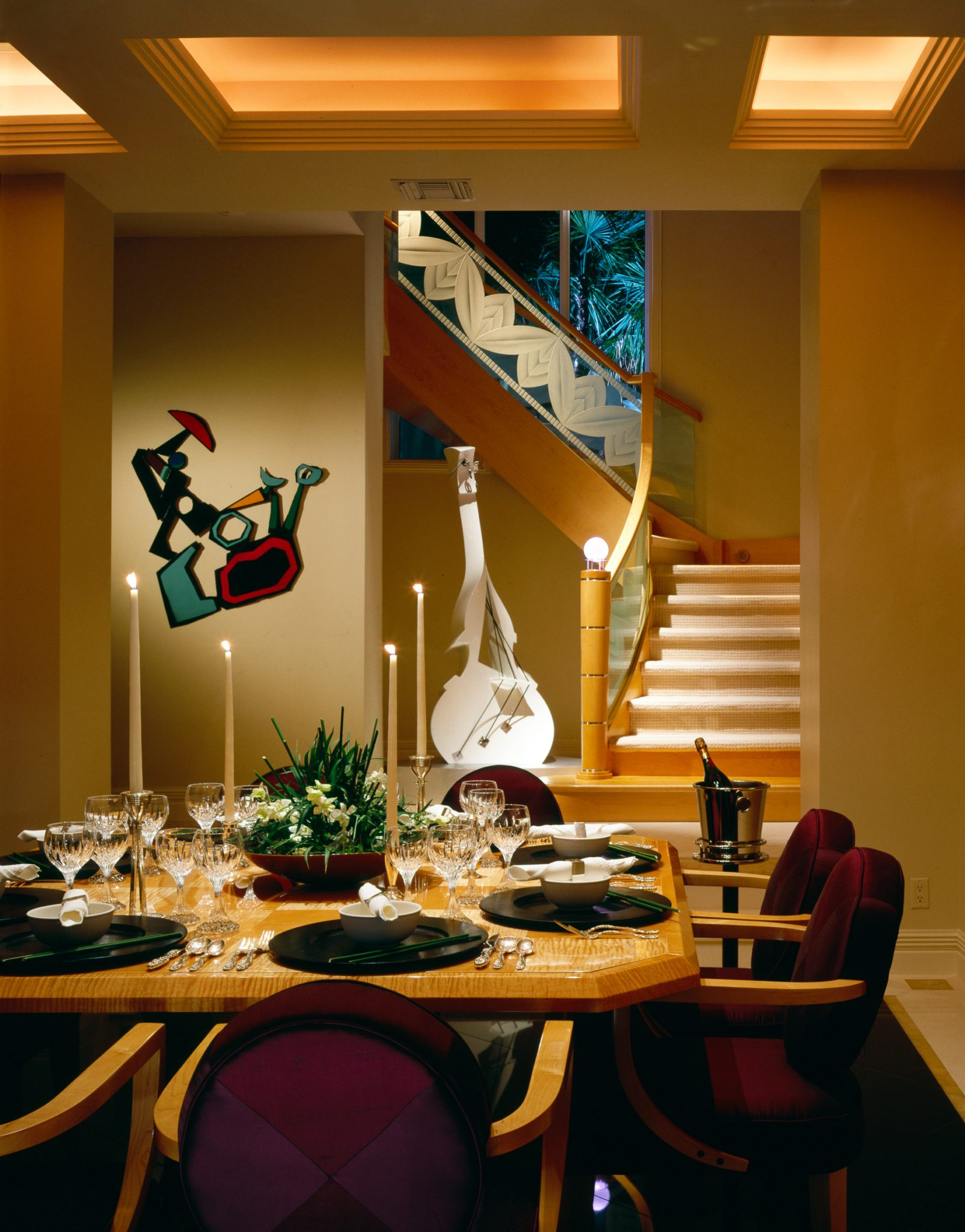 Custom wood and glass stairway is the backdrop for this contemporary dining area by Alene Workman Interior Design