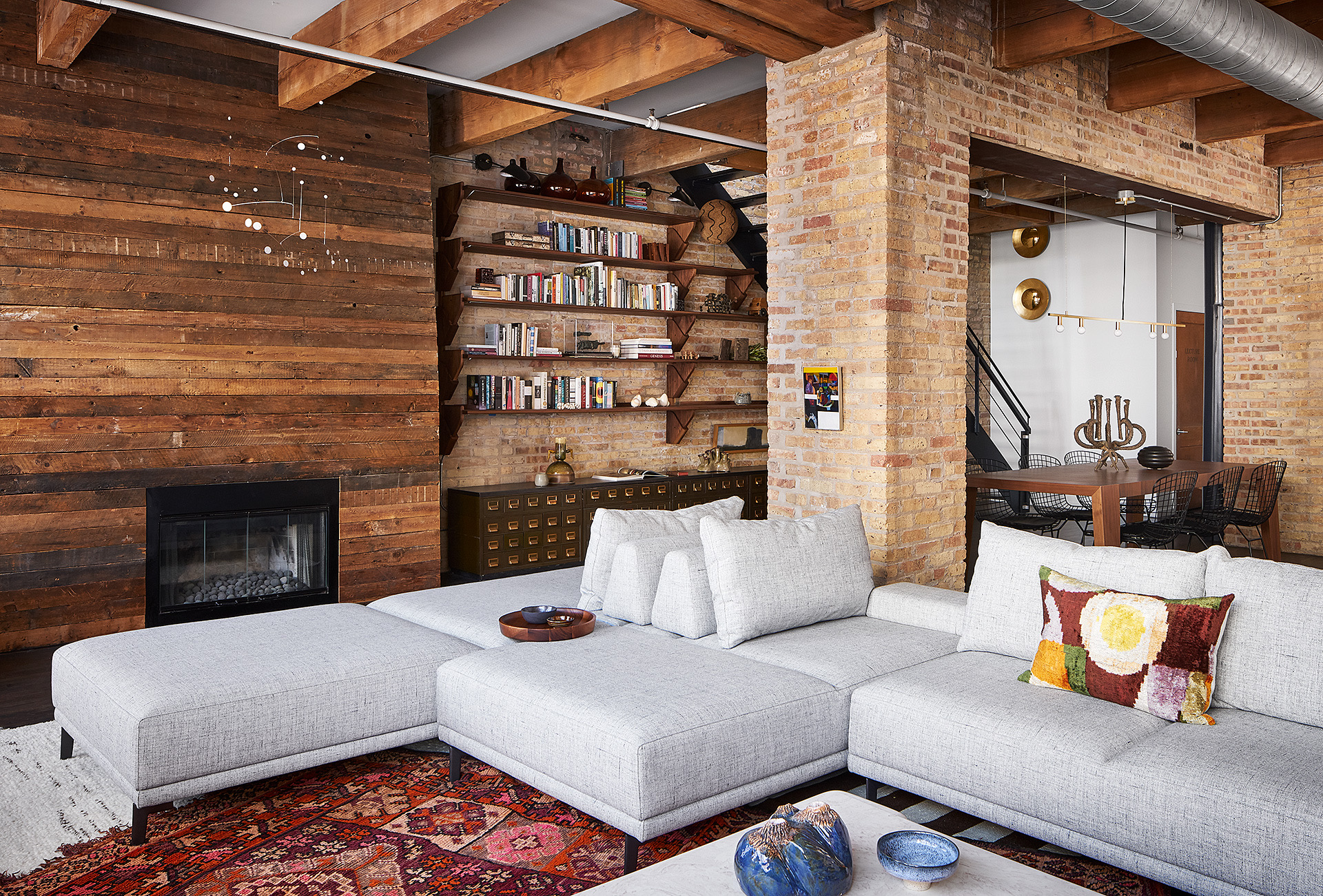 """Add Personal Details   To create an industrial-style space that feels warm and livable, create a setting that feels intimate and personal to the homeowner — """"either with curated vignettes or with heirloom and customized pieces that add an emotional connection to the environment,"""" says Melott.  Whether it's with curated artwork, a personal library, or framed family photographs, use items that reflect the homeowners to give the space a warm and comforting touch. """"Personal items that reflect the homeowner's preferences allow the space to stand out as being uniquely appointed,"""" says Andrea Michaelson of Andrea Michaelson Design. """"When using an industrial space that has industrial finishes as a background, you need to add more homey items to give it some soul and counterpoint."""""""