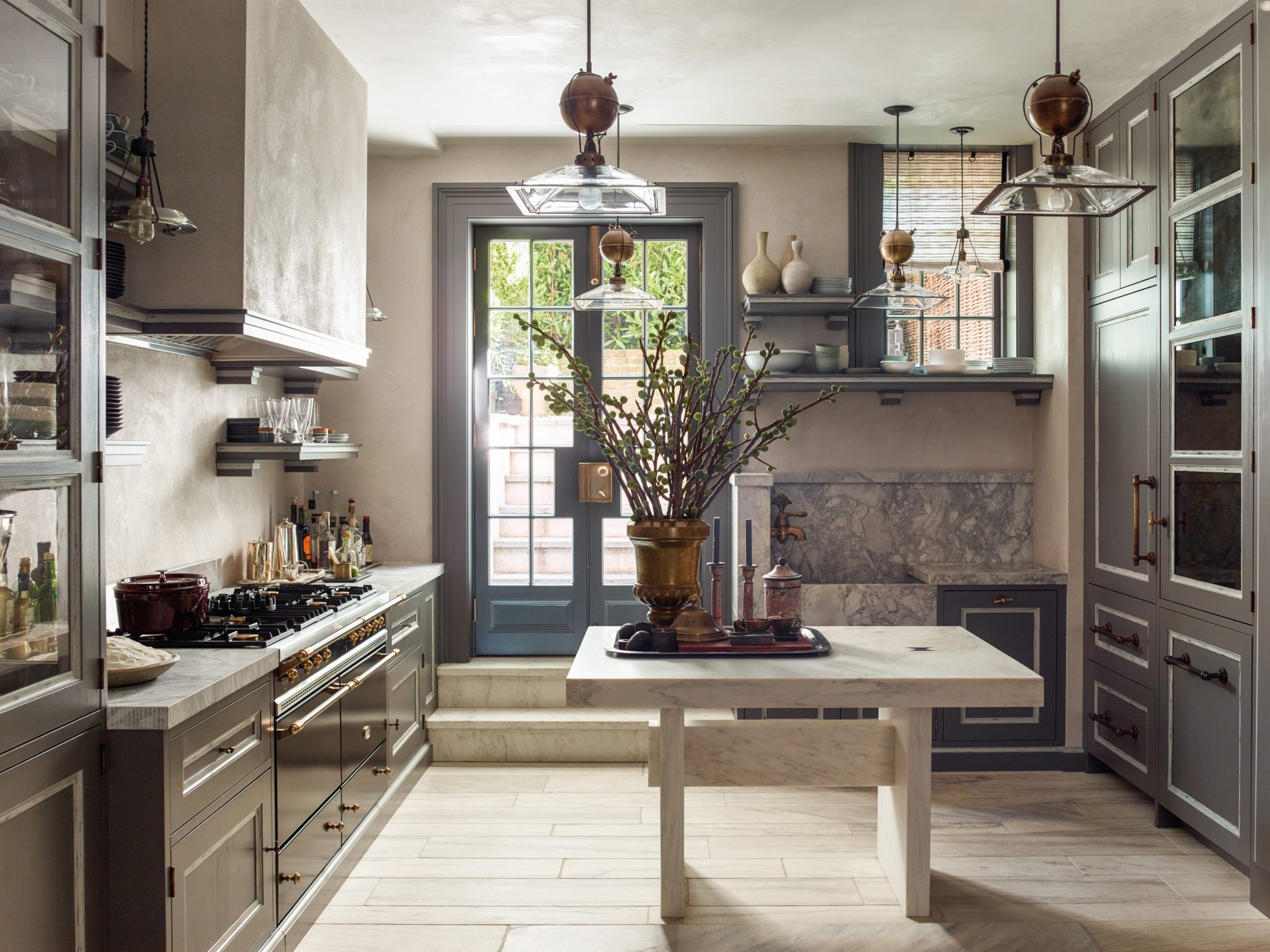 The renovation of the Morton Street townhouse involved lowering the kitchen floor by three feet to gain ceiling height and access to the garden; the custom cabinetry and shelves display hotel silver and everyday dishes.