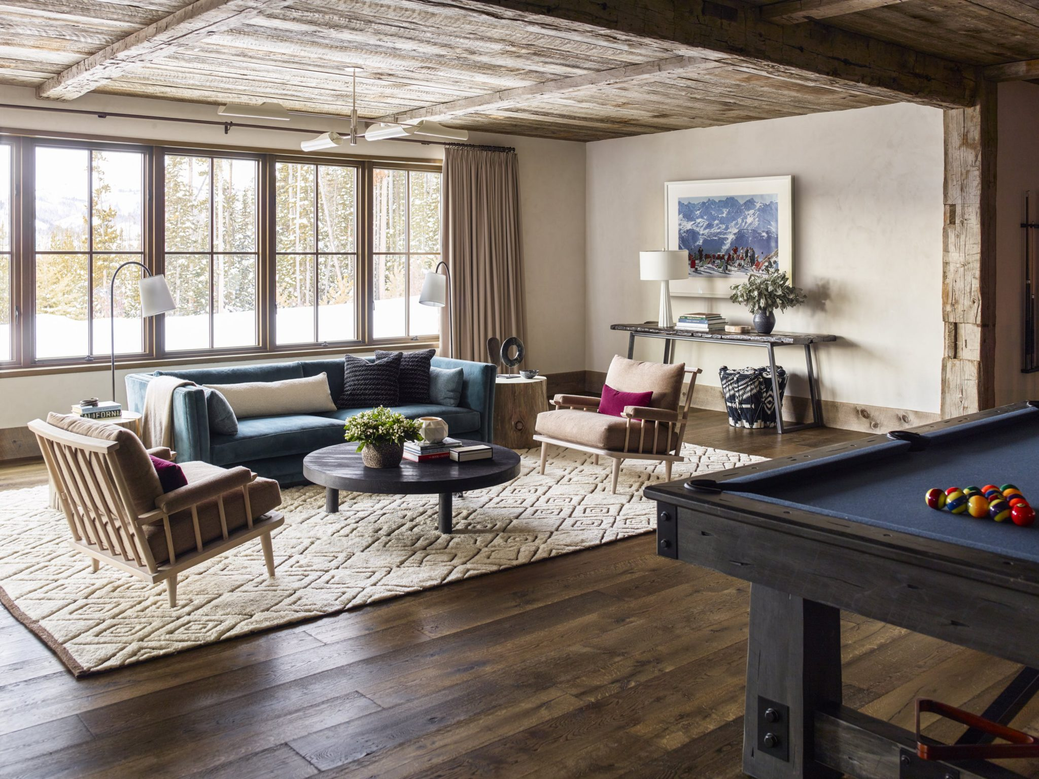 Enter the rec room, where a stylish pool table creates another great space for entertaining — as does the plush seating designed by Nickey Kehoe. The geometric rug from Stark brings texture to the space, while the pendant from David Weeks Studio and table lamp from GT Atelier add a modern touch.