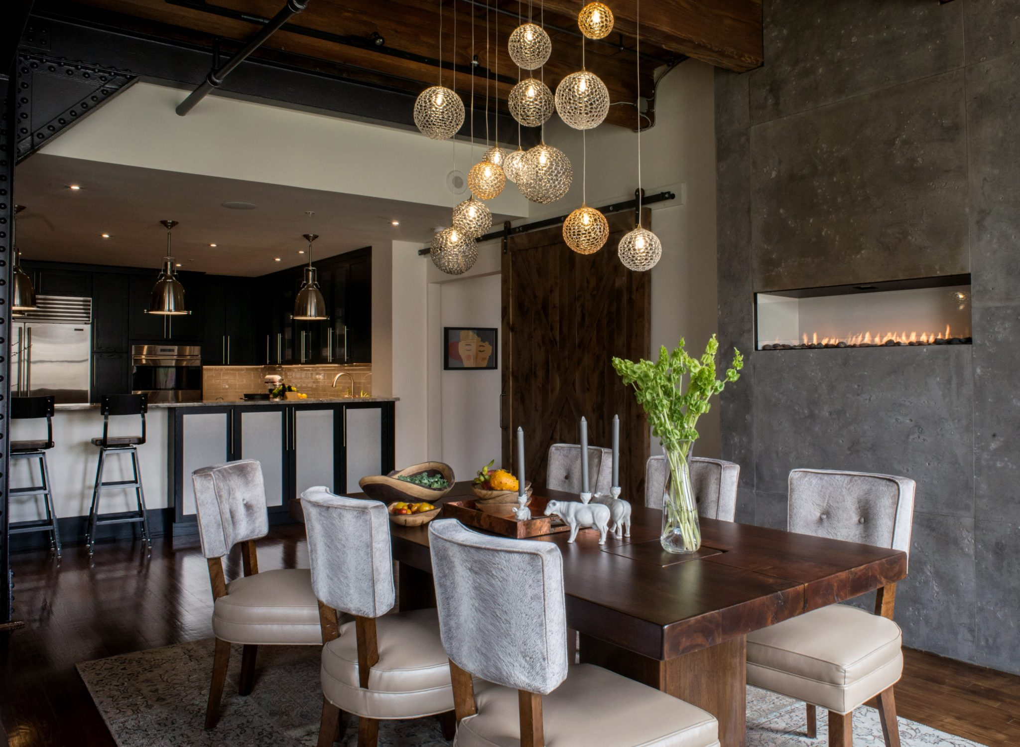 """Find the Right Lighting   When it comes to lighting an industrial space, think big and bold. """"Little fixtures get lost in big, high-ceiling spaces, especially pendant fixtures which need to be bigger and bolder than what you would use in a residential space,"""" says Lagrange. """"The same principles apply to floor and table lamps; they may need to be larger, more graphically bold and powerful than what would work in residential spaces.""""  In the above image, designer Michele Plachter uses a hand-blown glass chandelier to create a focal point over the dining room table. """"I am a huge believer that lighting is the jewelry in any space. The hand-blown glass globes we sourced are perforated so when the light is on, it reflects light patterns that sparkles at night and reflects off of the walls,"""" she says.  To create additional warmth, Bishop advises designers to use fixtures and bulbs with dimmers. """"One of the biggest design elements that can be used to add warmth to a space is often the most overlooked one: lighting. Lighting types and how they affect the overall feel of a space is important. Use warm decorative lighting on dimmers and avoid cool LEDs or only recessed downlights,"""" she says."""