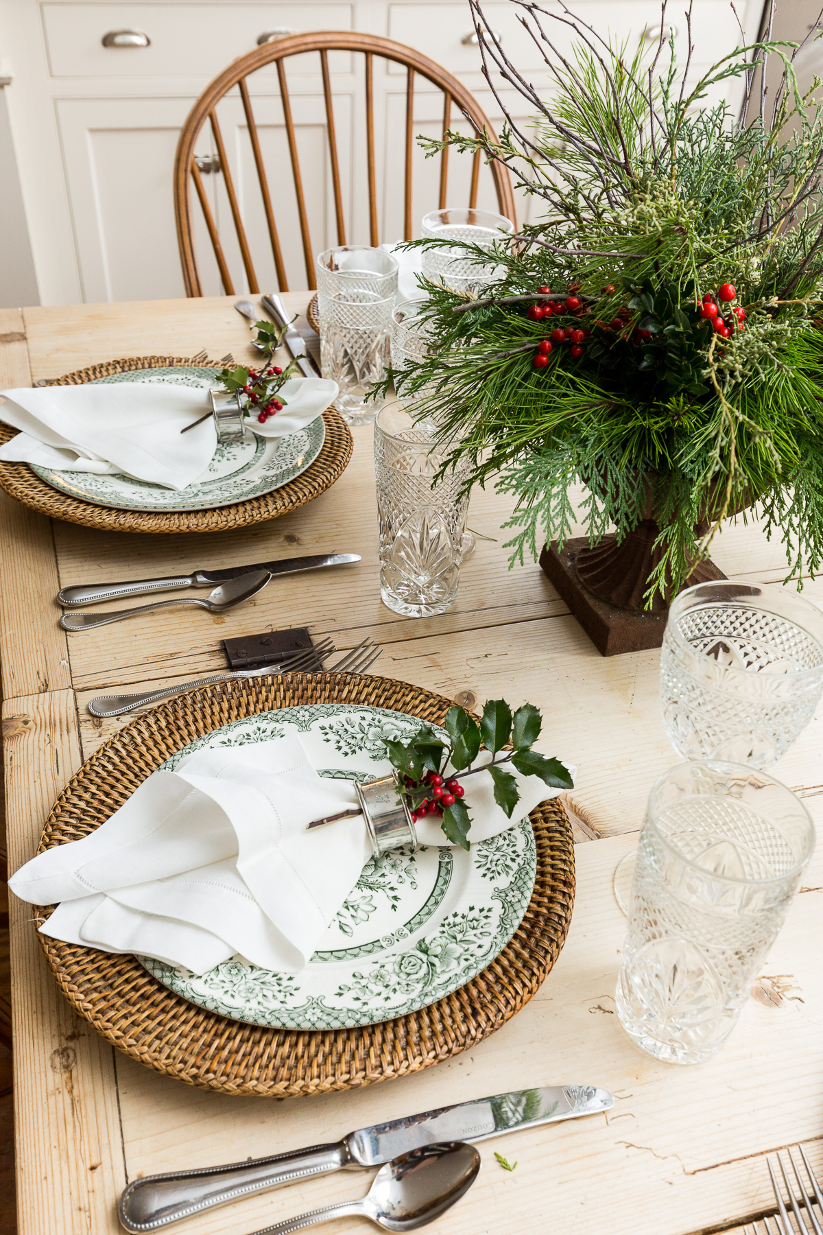 A farmhouse table features holiday greens; layered with organic textures. by Reed & Acanthus Interior Design