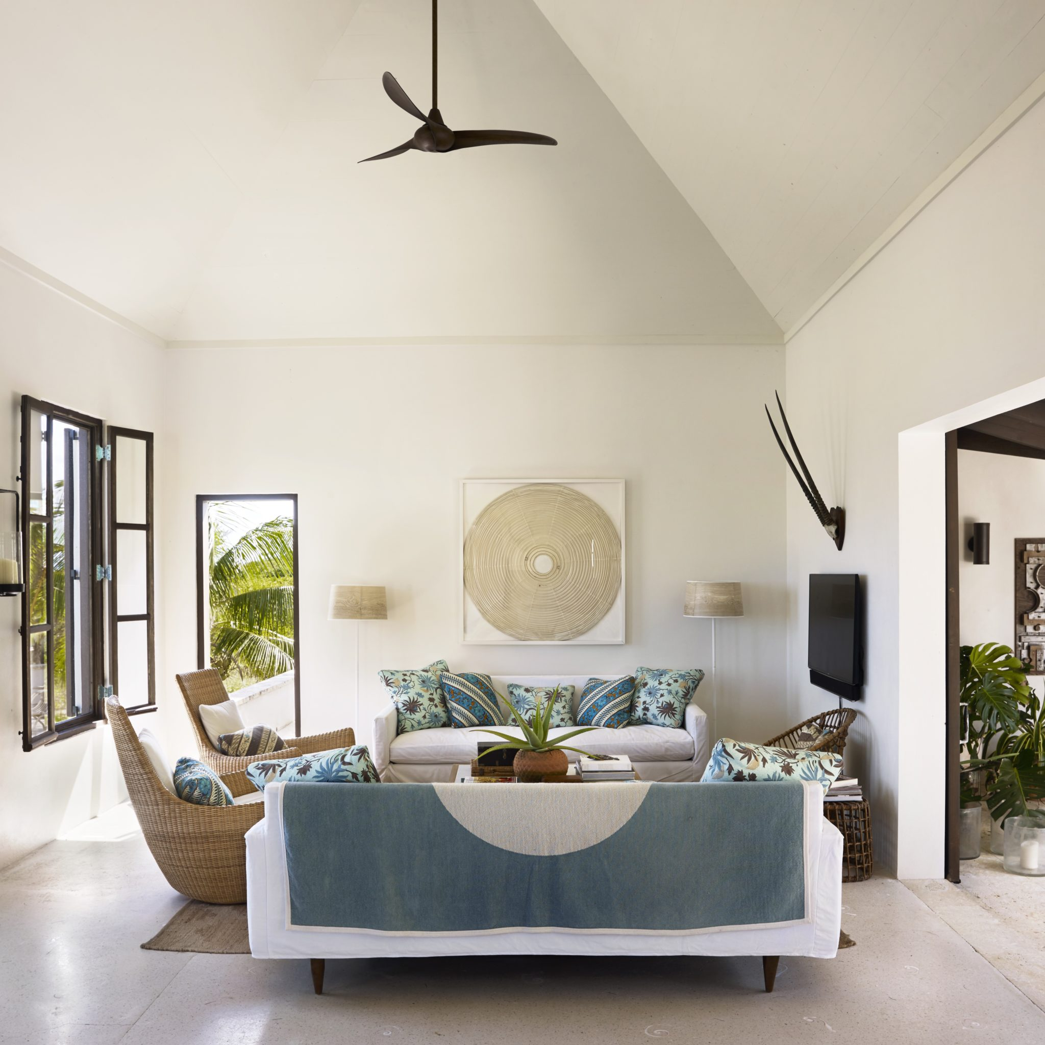 "In the living room of the designer's own vacation house on the Bahamas' Abaco Islands, the matching sofas are covered in white duck slipcovers; a pair of woven rattan ""rockers"" face a courtyard and the television crowned with oryx horns."