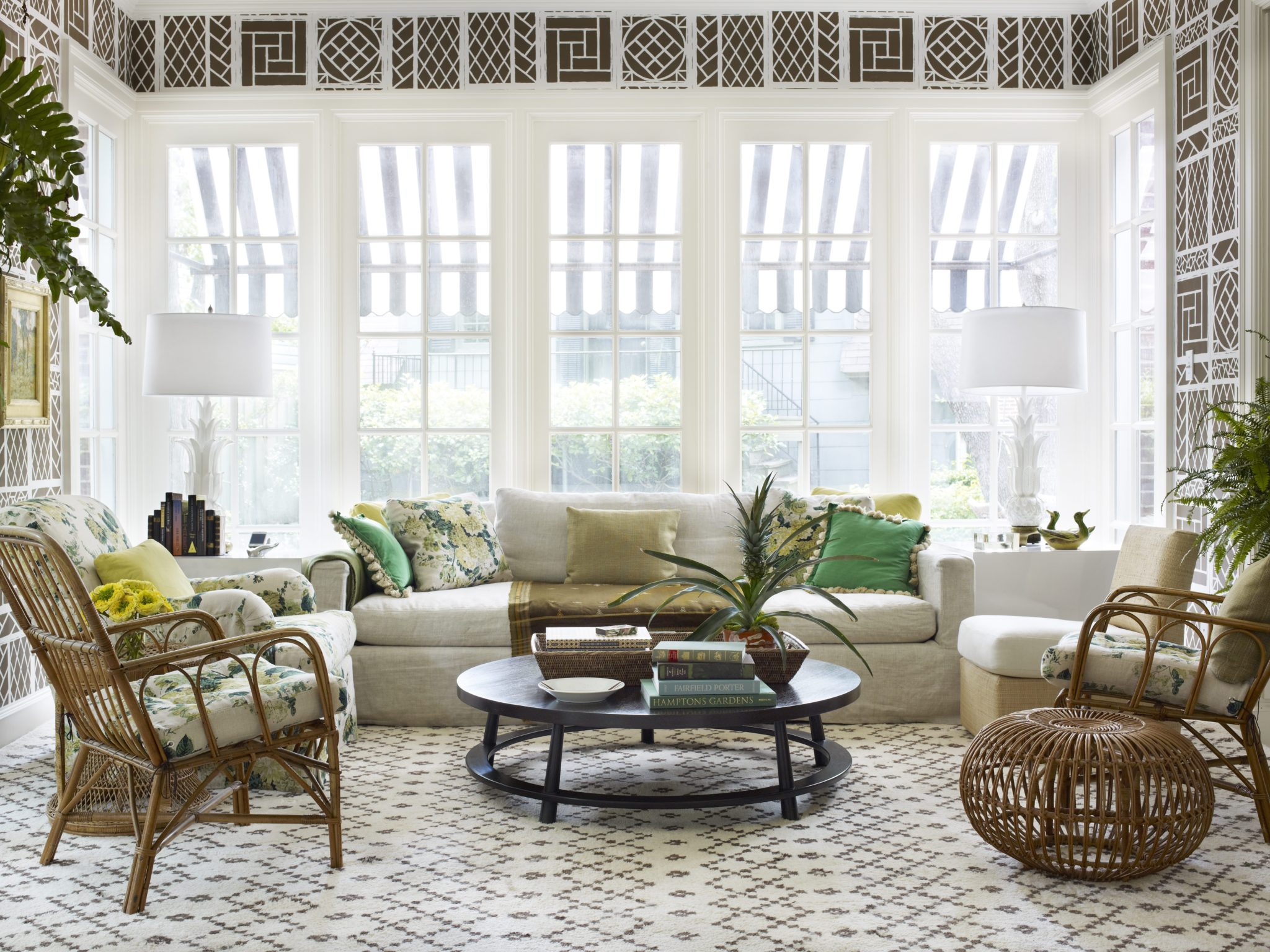 The sunroom of a 1930s Georgian house in Dallas is shaded by retractable black-and-white-striped awnings. The designer's favorite Lyford Trellis wallpaper was rescaled and recolored for both the sunroom and the adjacent dining room. The round coffee table by Robsjohn-Gibbings is surrounded by an artful mix, including a Billy Baldwin slipper chair, antique wicker chairs, a Restoration Hardware sofa, and a custom Bridgewater chair from Luther Quintana Upholstery. The end tables are simple painted plywood boxes.