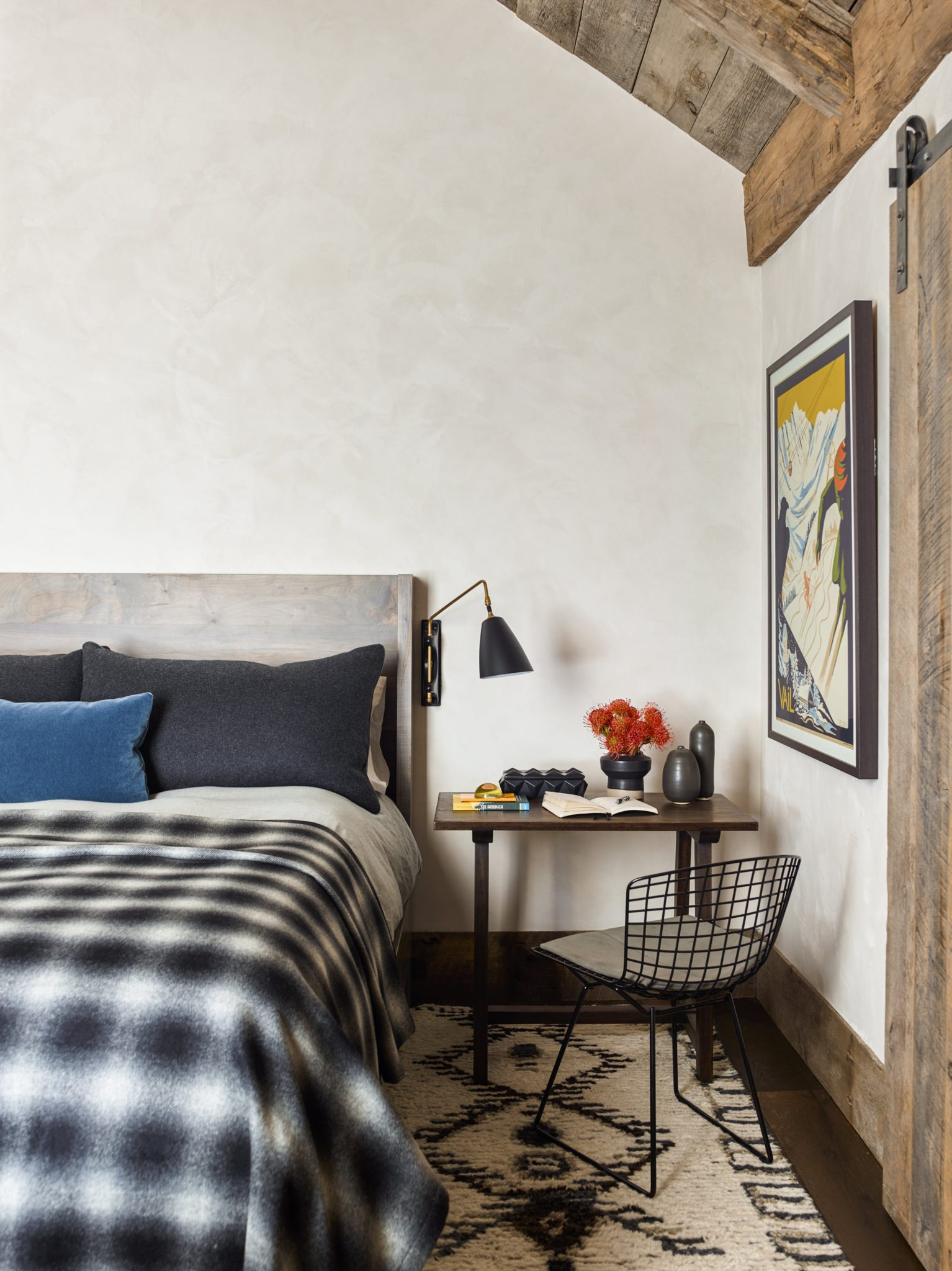 The guest bedroom displays a cozy, contemporary design. The walnut bed from BDDW is decorated with a custom bed cover in Chivasso plaid and pillows in Mariano Fortuny mohair and Jean de Merry wool. The brass swing arm sconce is from Obsolete and the metal desk chair is from Harry Bertoia.